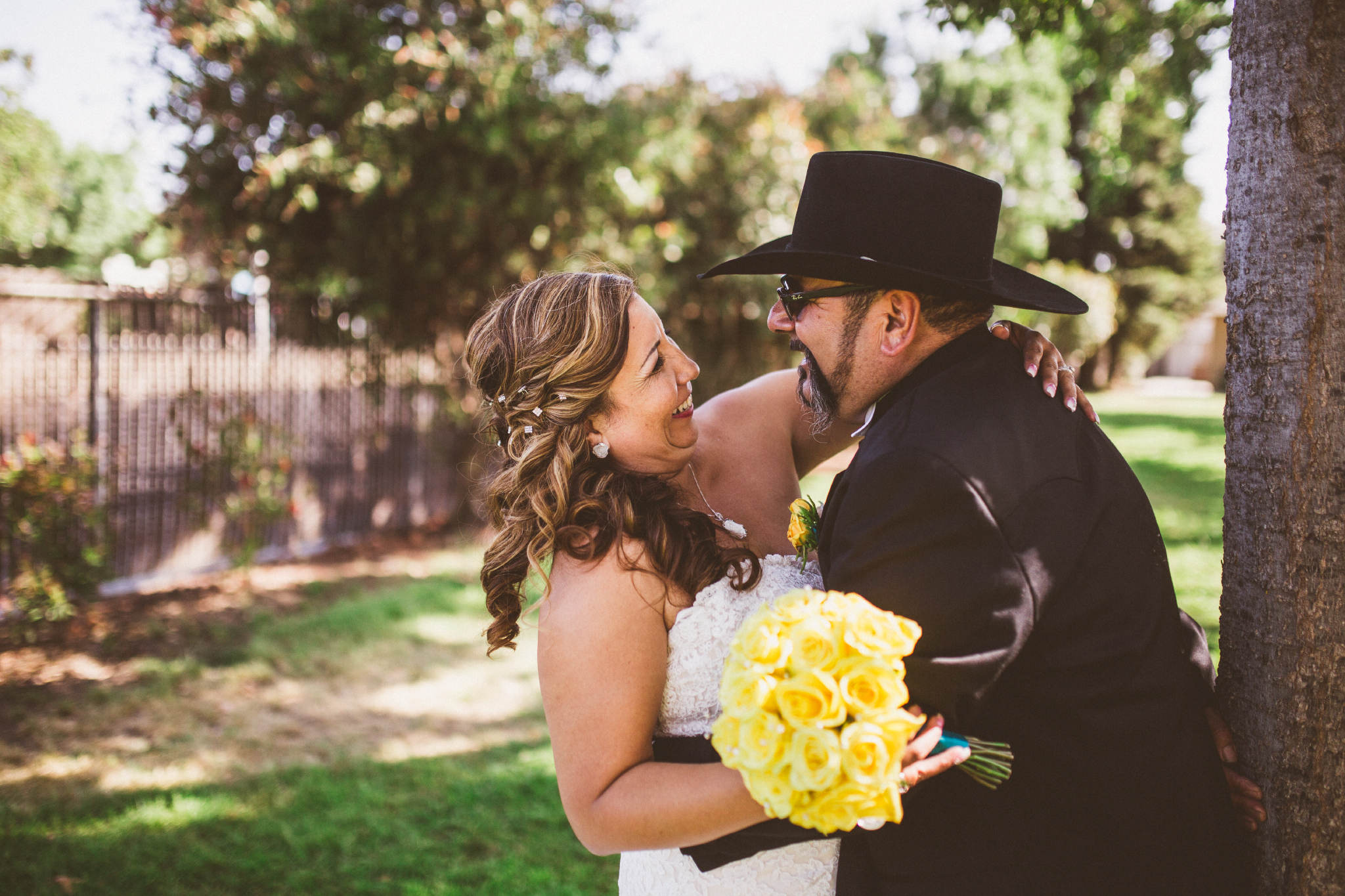 san diego wedding   photographer   groom with cowboy hat laughing hugging bride leaning against   tree