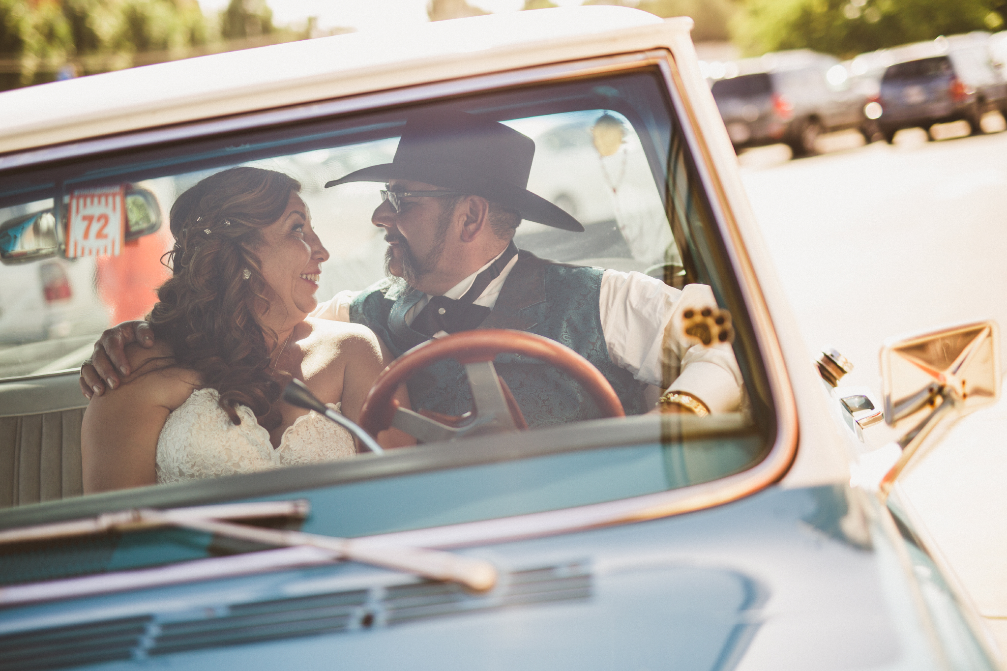 san diego wedding   photographer   groom with cowboy hat and bride facing each other and smiling   blue pickup truck