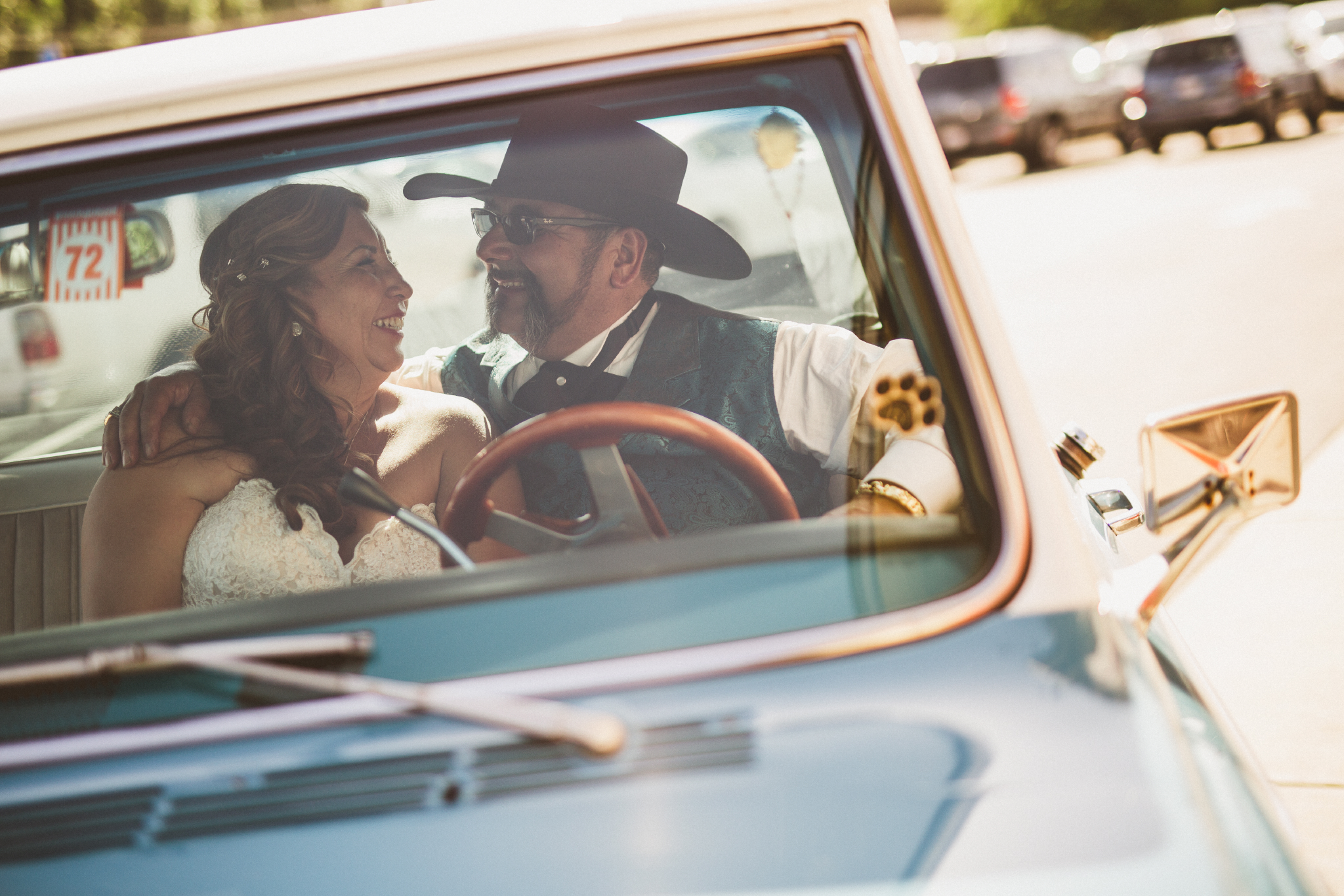 san diego wedding   photographer   groom with cowboy hat and bride facing each other and laughing   inside blue pickup truck