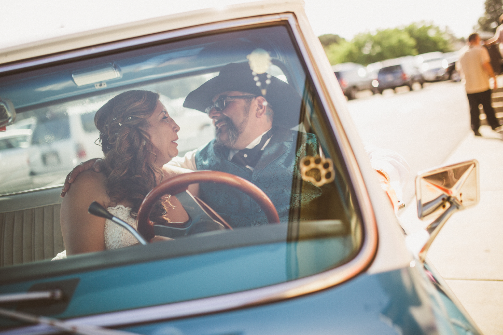 san diego wedding   photographer   groom with cowboy hat and bride facing each other and laughing   inside blue pickup truck with man in background