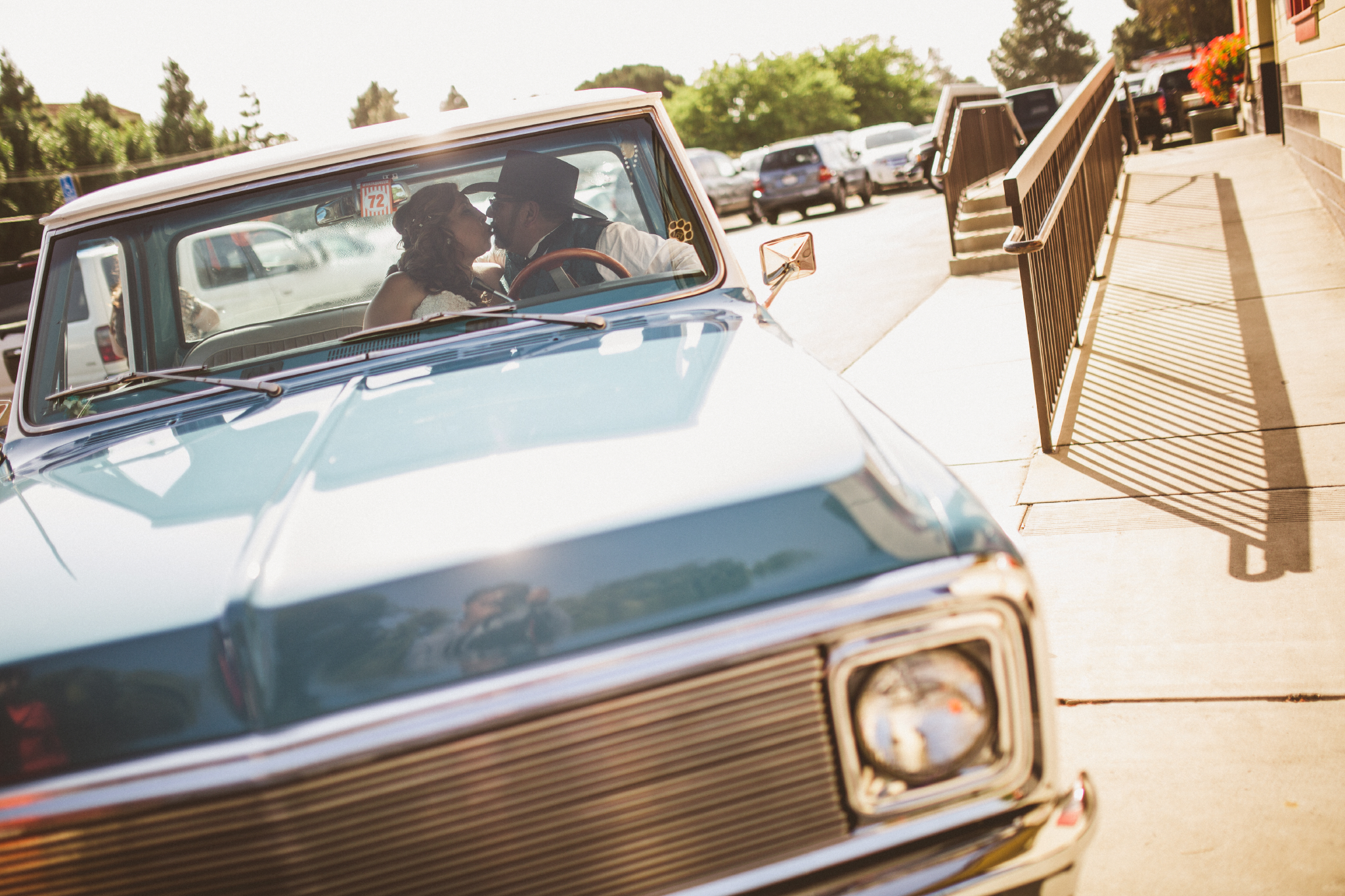 san diego wedding   photographer   groom with cowboy hat and bride kissing inside blue pickup   truck