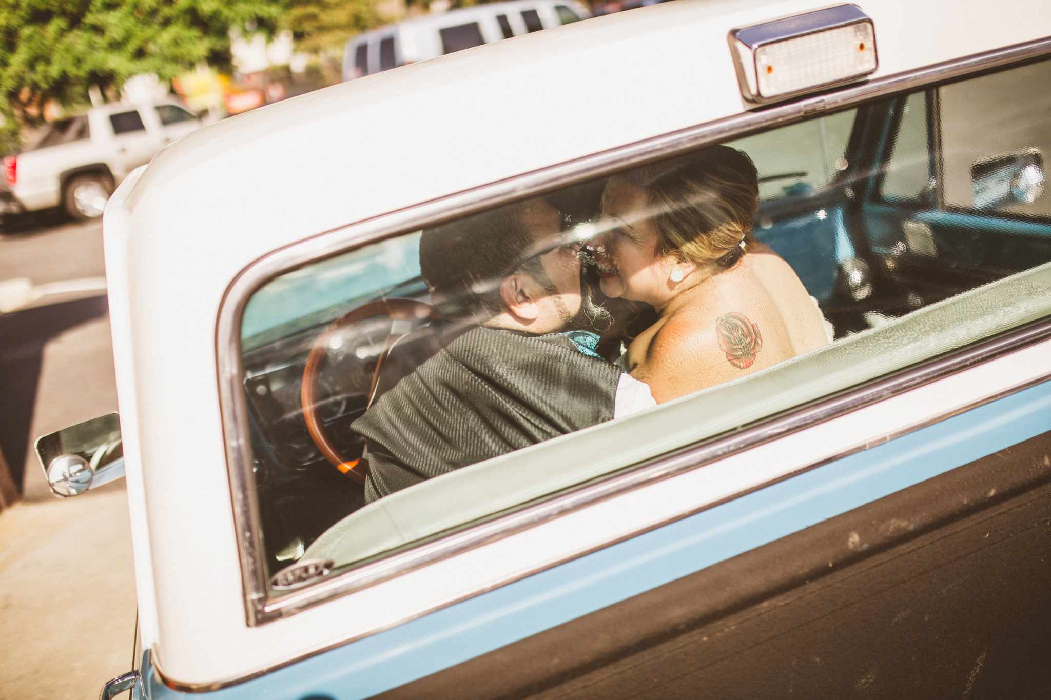 san diego wedding   photographer   couple laughing and about to kiss inside blue pickup truck
