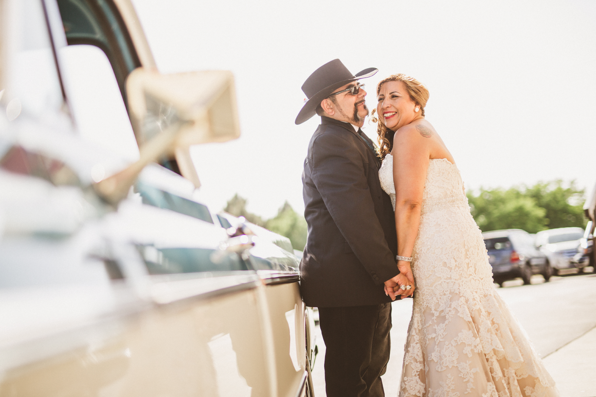 san diego wedding   photographer   groom with cowboy hat and bride holding hands and smiling   beside blue pickup truck
