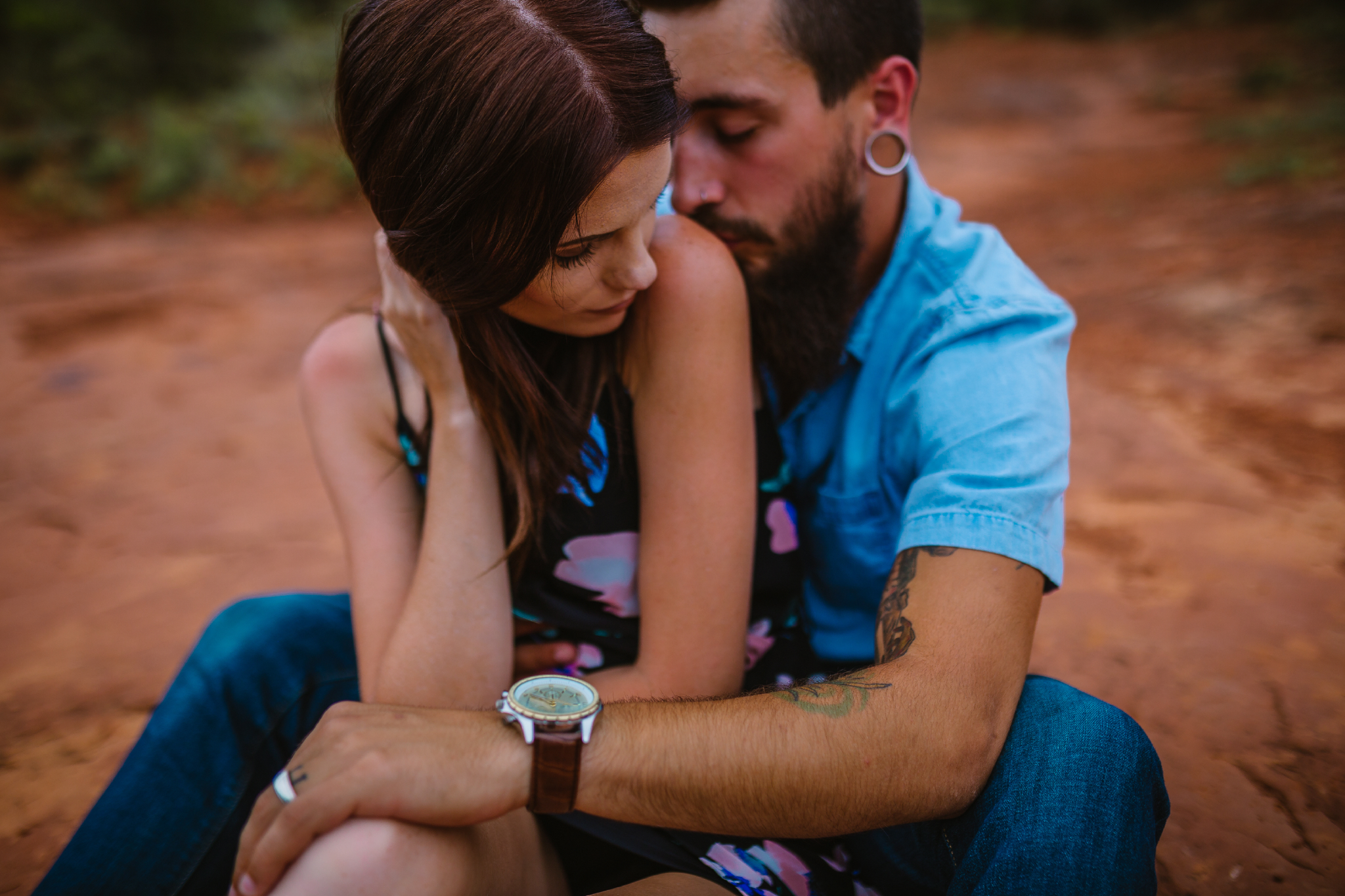 san diego wedding   photographer | bearded man in blue shirt and earrings hugging woman from   behind