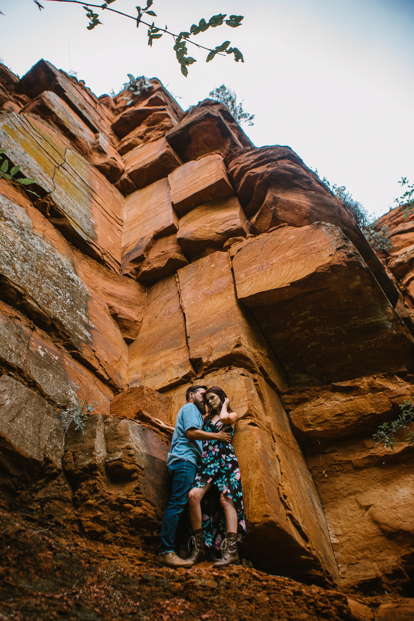 san diego wedding   photographer | bearded man in blue holding woman in black floral dress   against rock formation