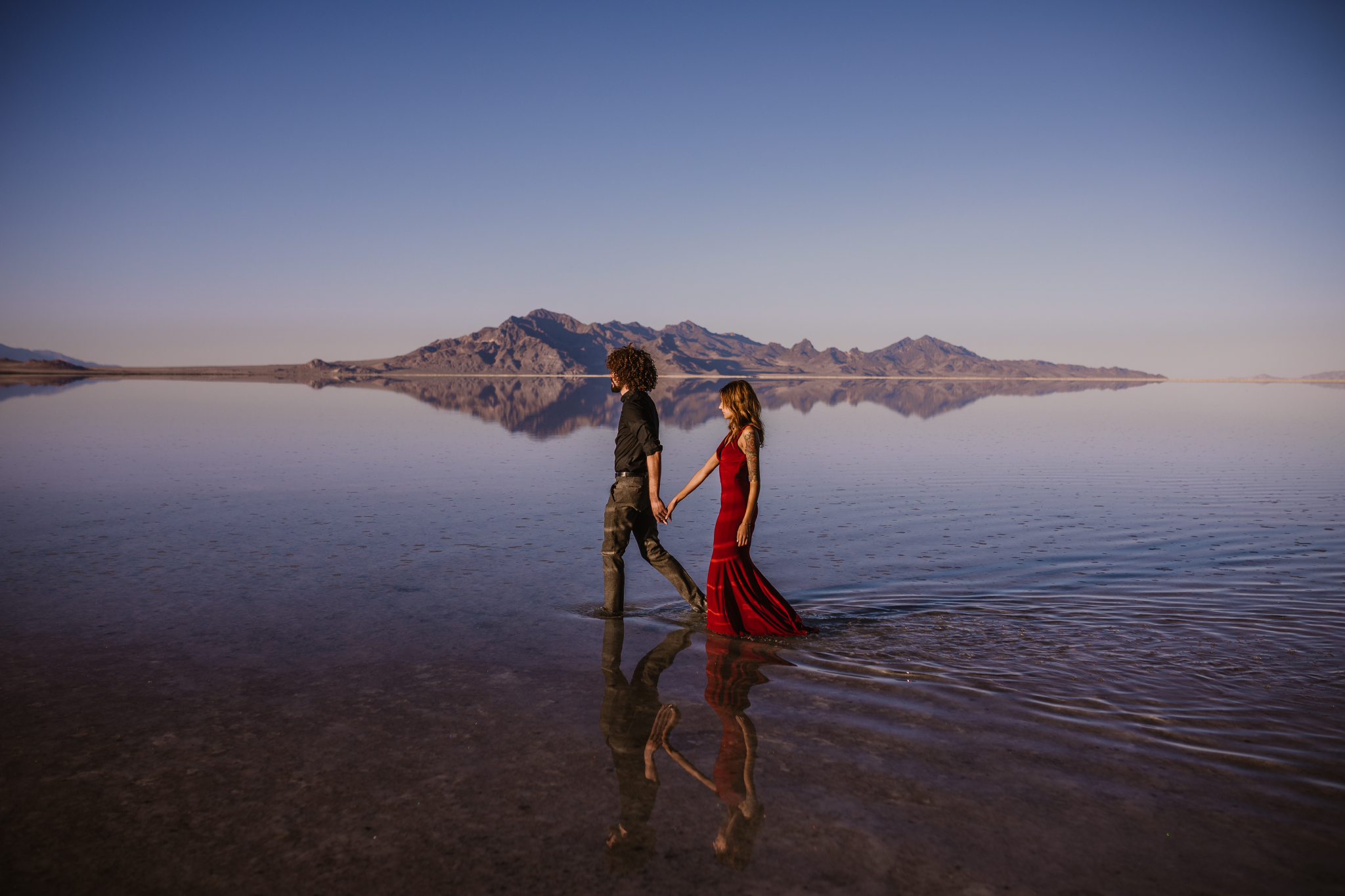 san diego wedding   photographer | side view of man in black polo holding hands with woman in red   dress walking on salt flats
