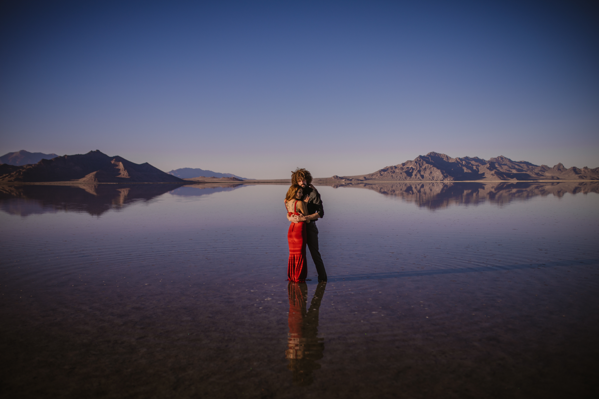 san diego wedding   photographer | whole body shot of woman in red dress embracing man in black   polo while standing on salt flats