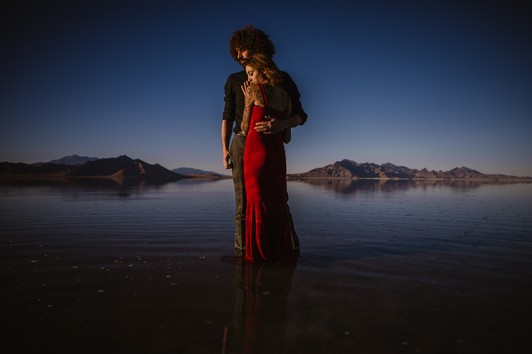 san diego wedding   photographer | close-up shot of woman in red dress embracing man in black   polo while standing on salt flats