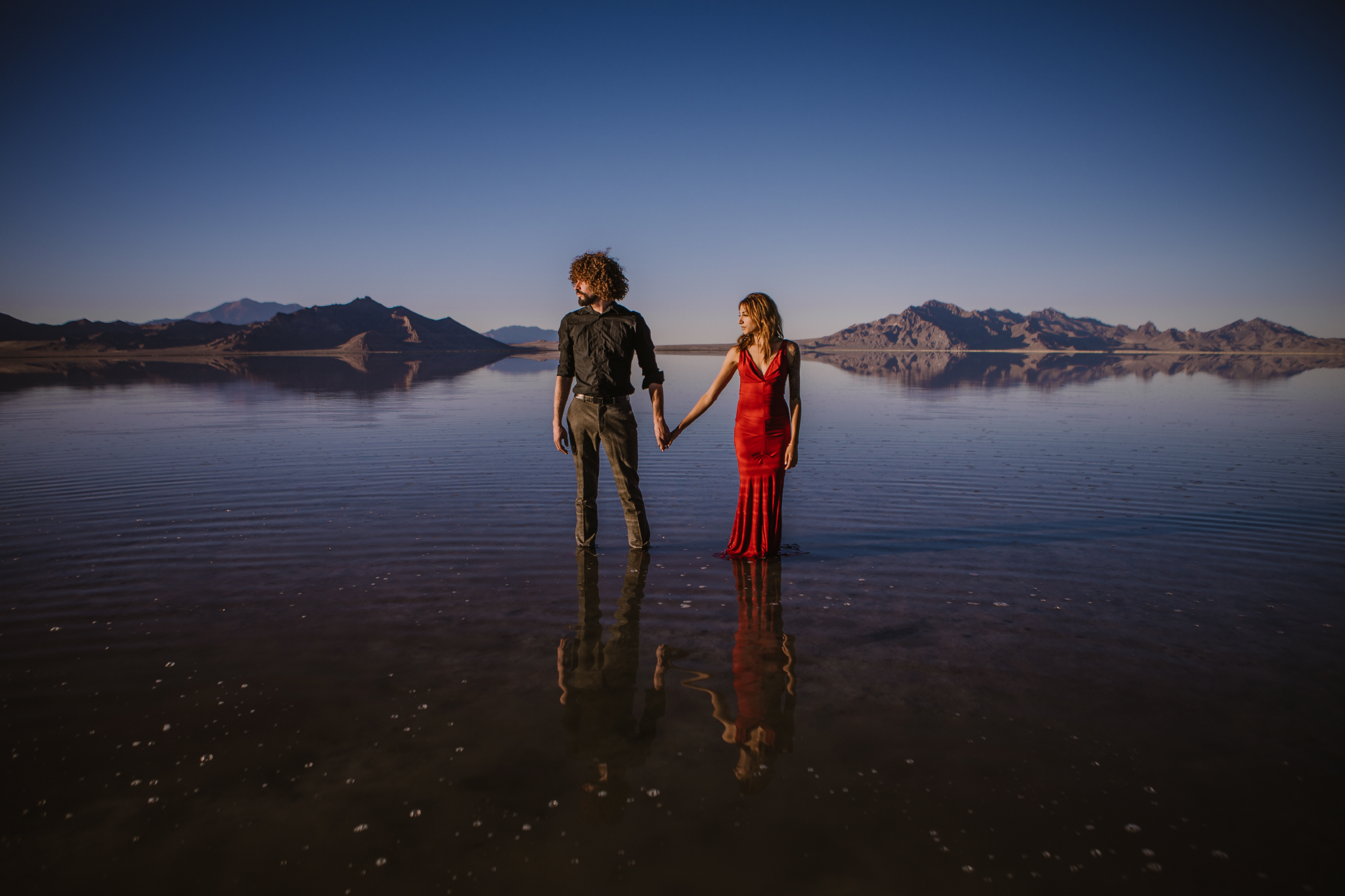 san diego wedding   photographer | front view of man in black polo holding hands with woman in   red dress facing the left and standing on salt flats