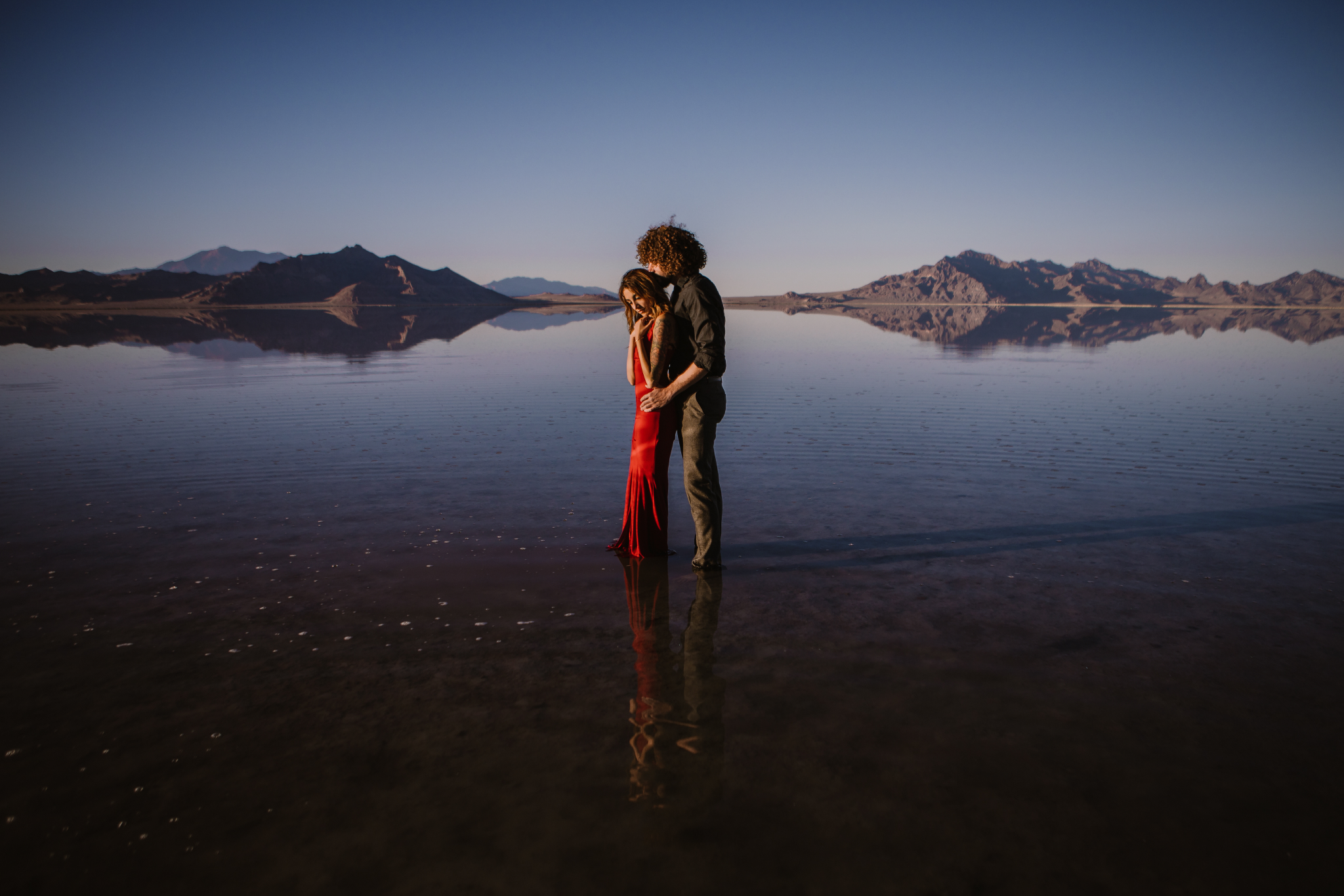 san diego wedding   photographer | side view of man in black polo holding waist and kissing head   of woman in red dress while standing on salt flats