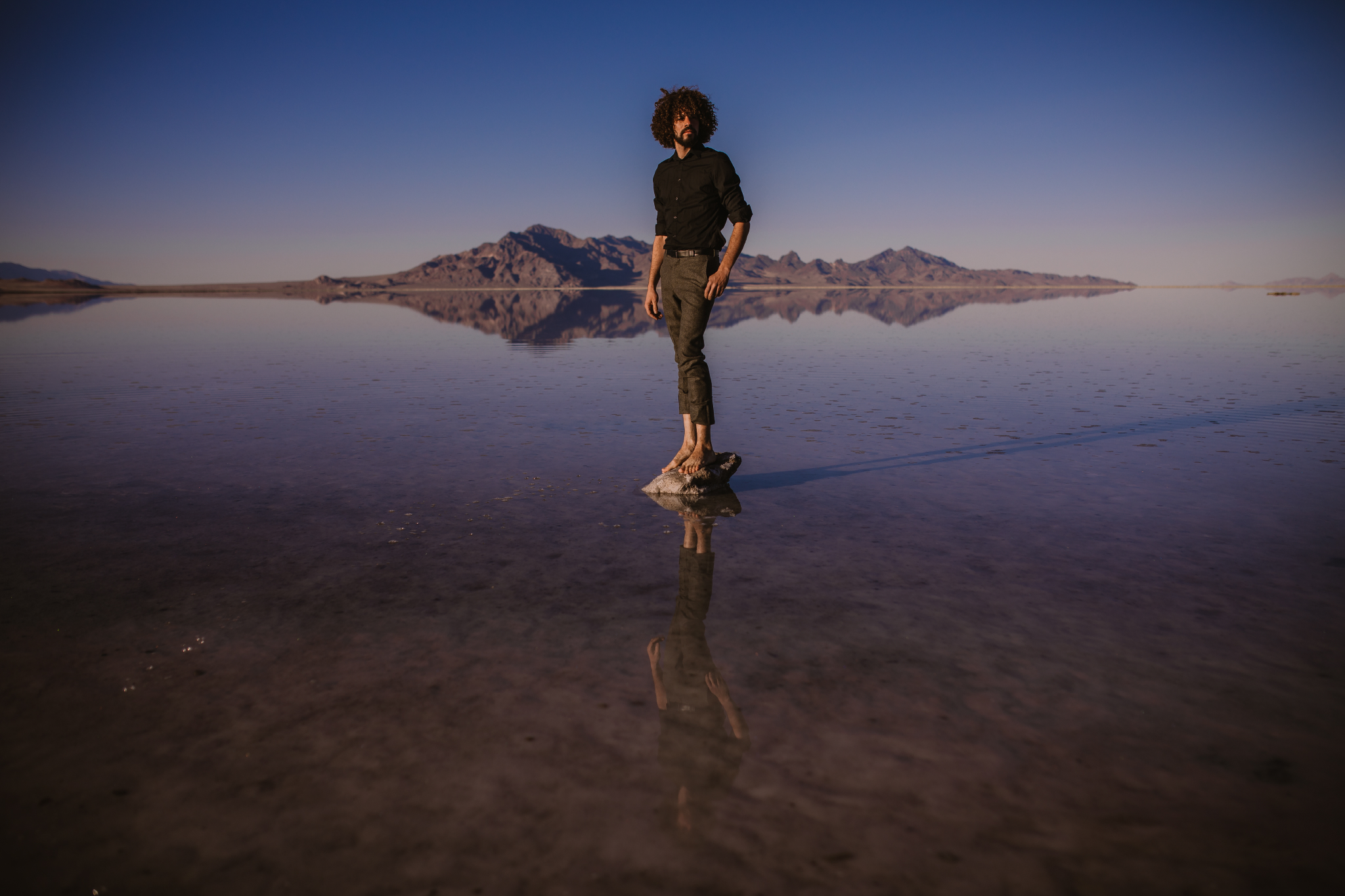 san diego wedding   photographer | man in black polo standing on rock on salt flats facing   forward with thumb in pocket