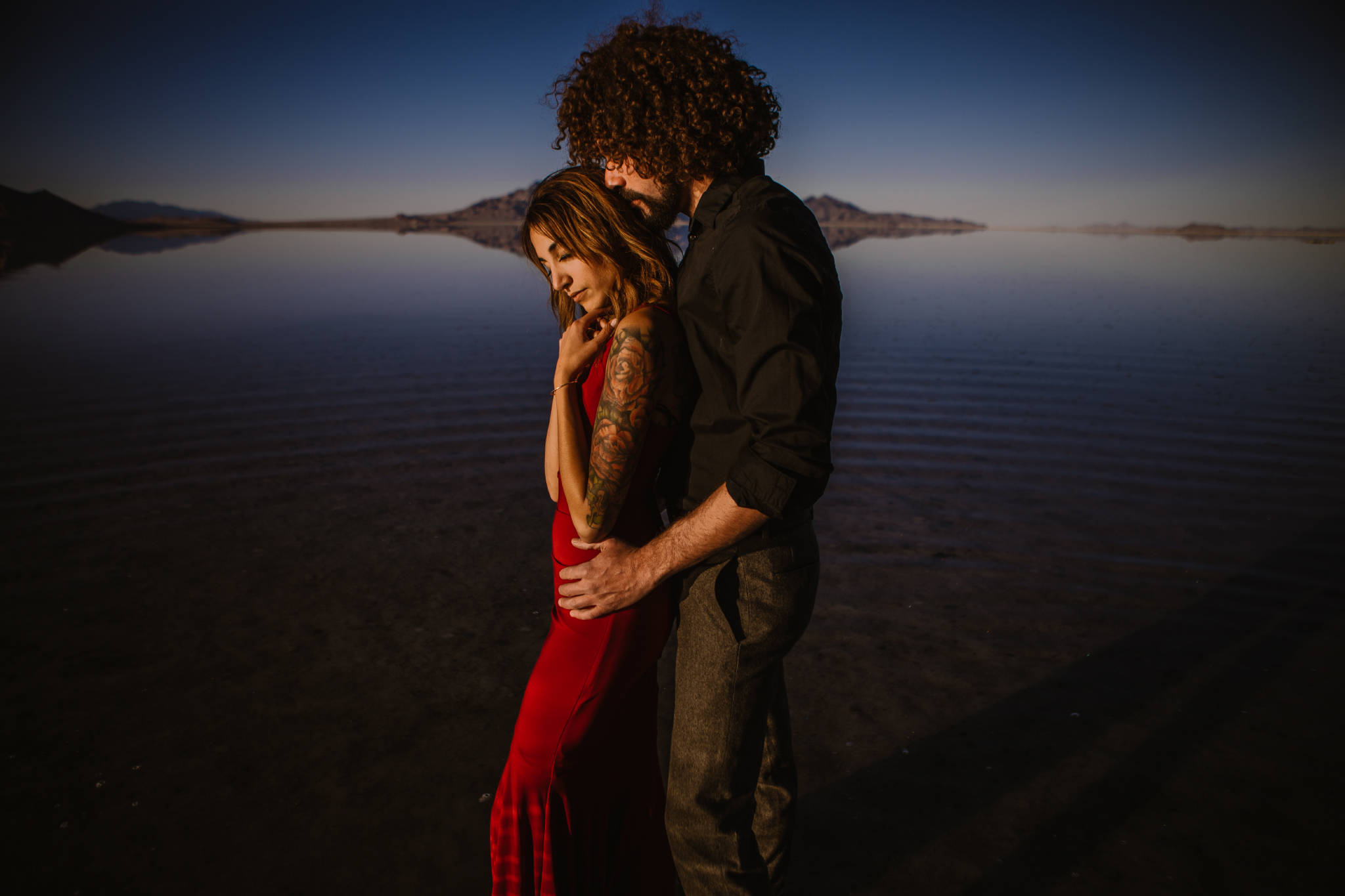 san diego wedding   photographer | close-up of man in black polo holding waist and kissing head   of woman in red dress while standing on salt flats