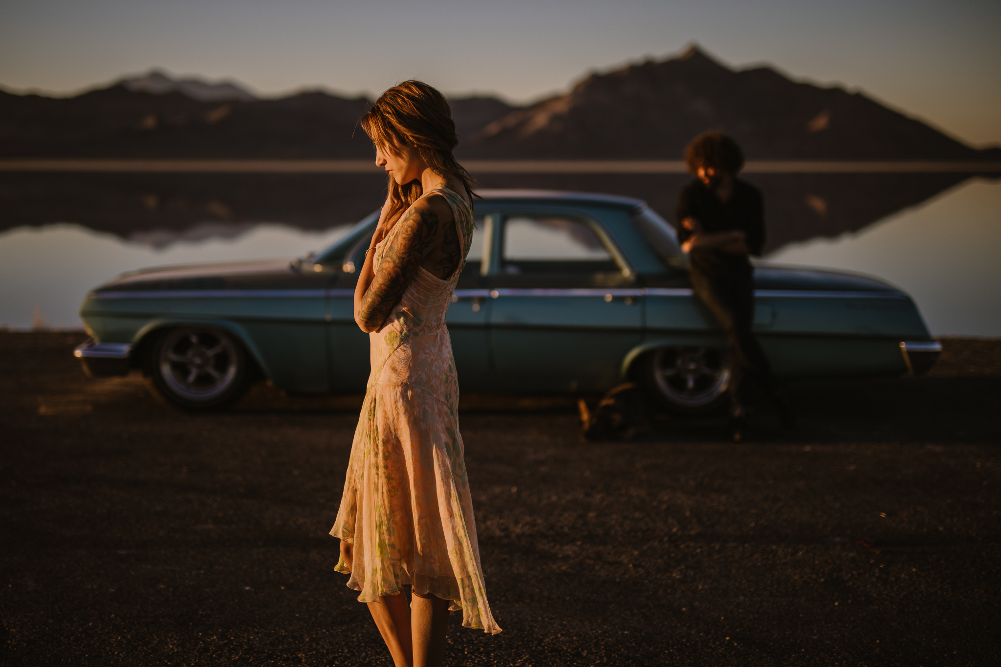 san diego wedding   photographer | side view of tattooed woman in pink dress facing the left with   man in black polo and blue vintage car in background