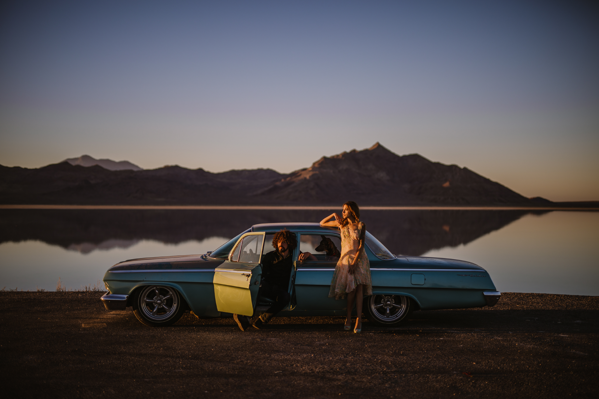 san diego wedding   photographer | side view of vintage blue car with man in black polo sitting   on driver's seat and tattooed woman in floral dress leaning her elbow on the   car with dog in backseat