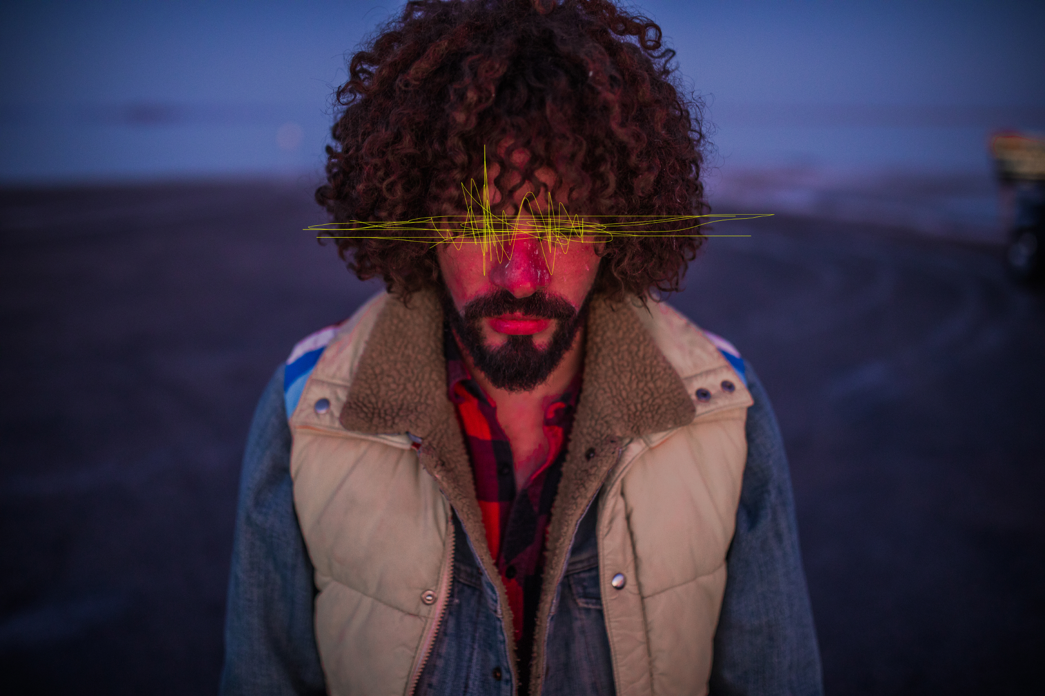 san diego wedding   photographer | man with curly hair and beige vest over a denim jacket facing   front with yellow waves edited over his eye