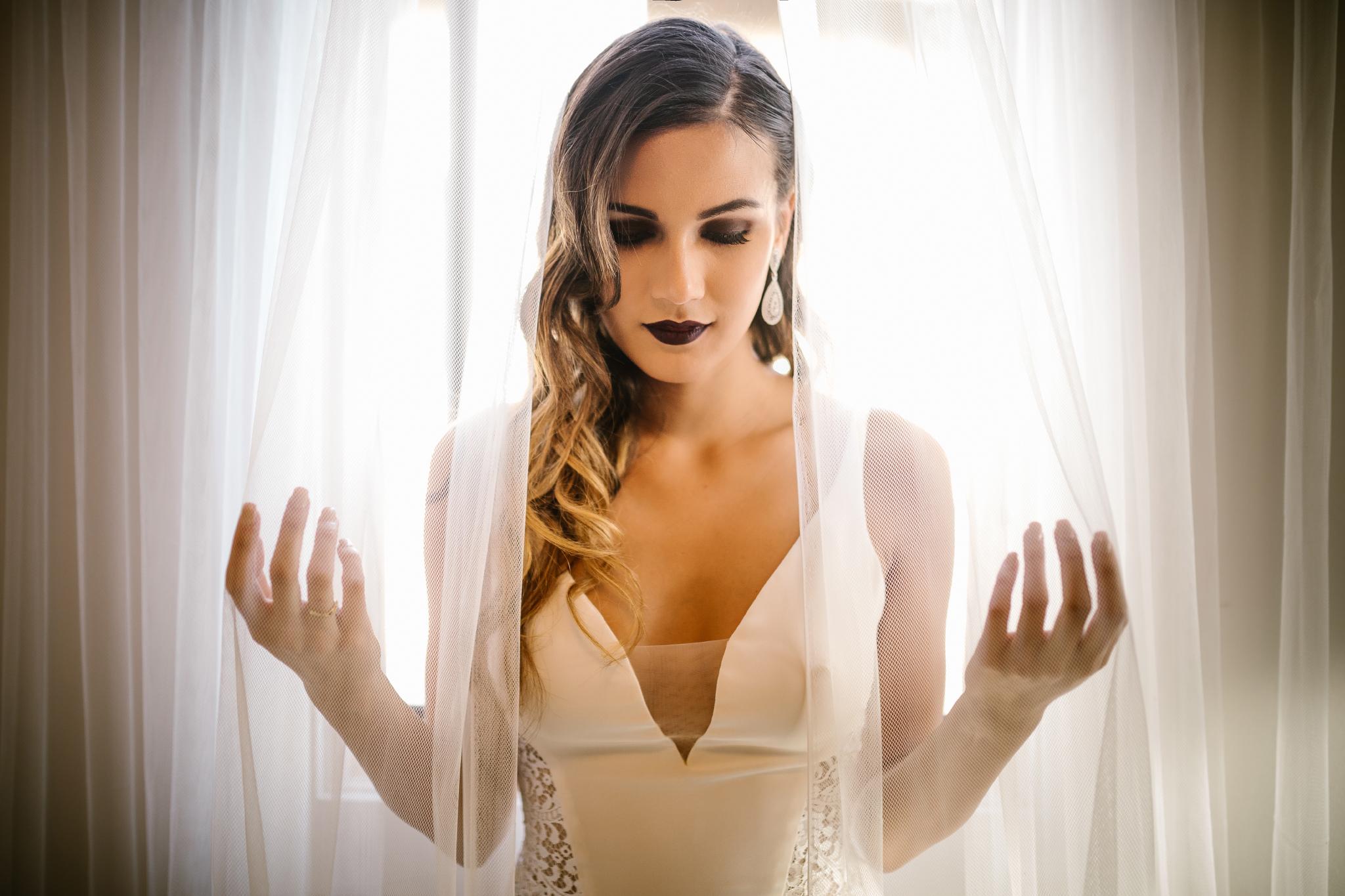 san diego wedding   photographer   woman in dark lipstick behind curtains