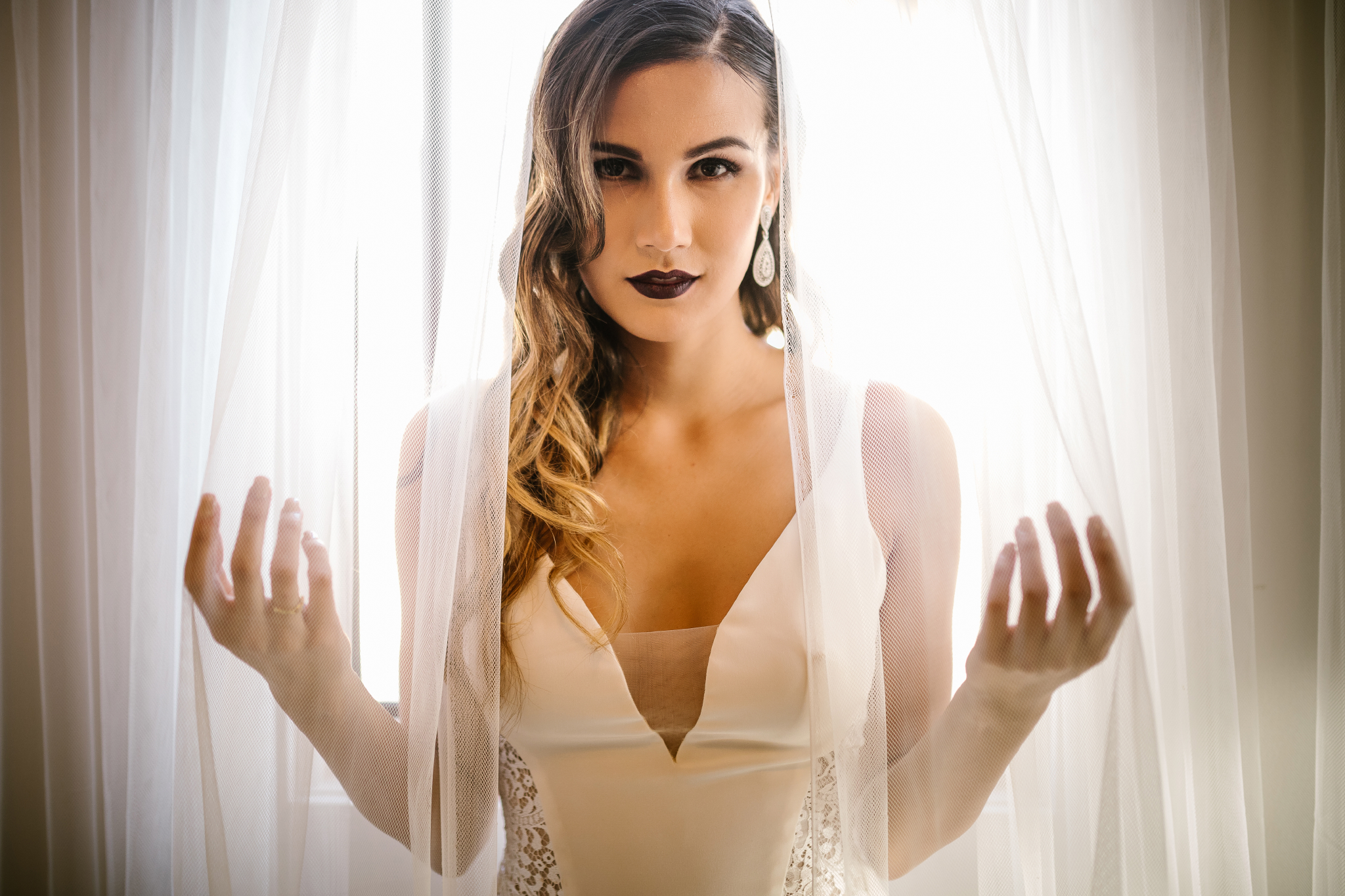 san diego wedding   photographer   woman in dark lipstick behind curtains looking at the camera