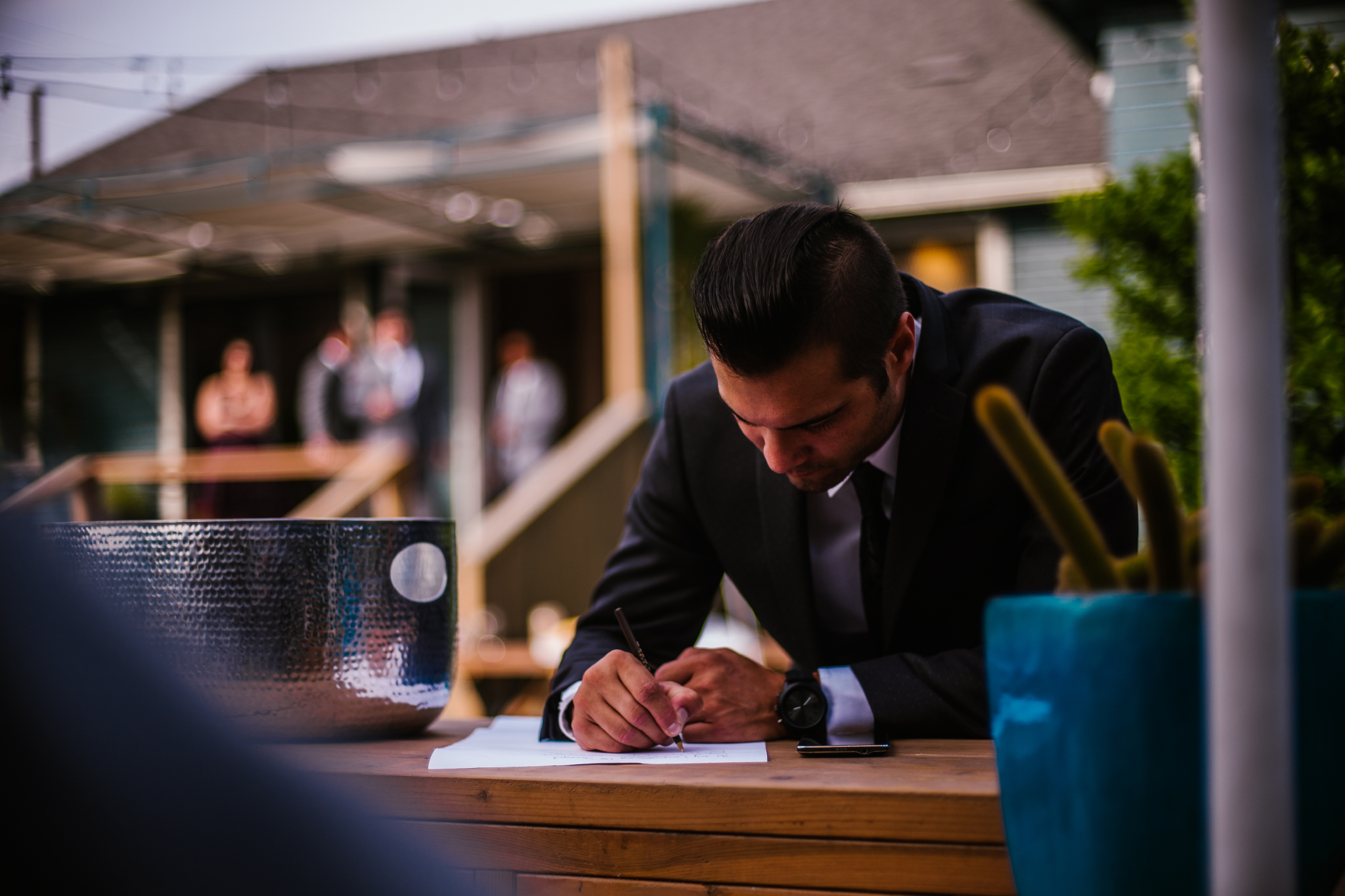 san diego wedding   photographer   groom concentrating writing something