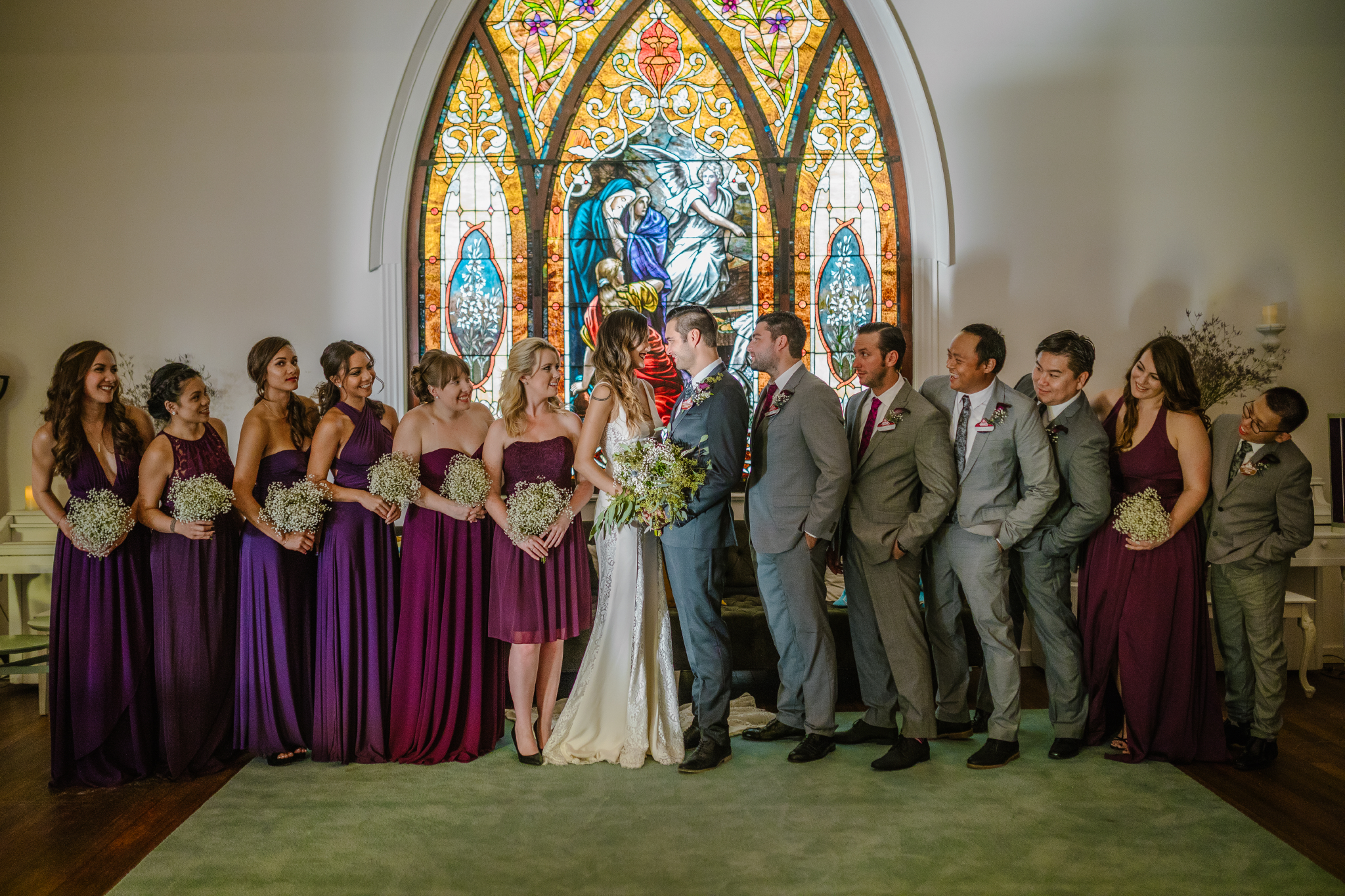 san diego wedding   photographer   bridesmaids and groomsmen lined up in front of stained glass