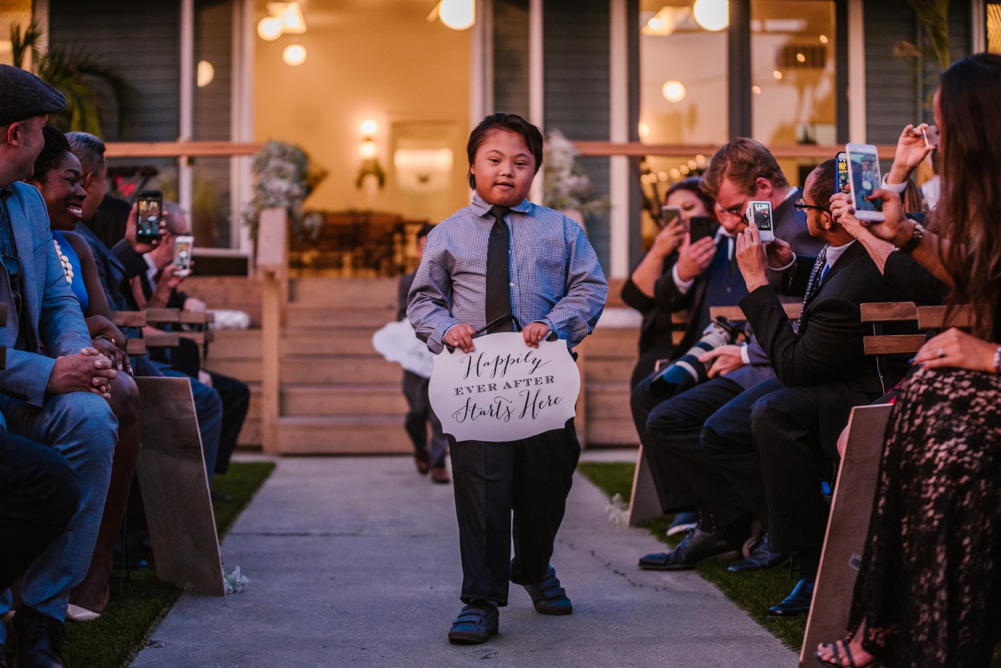 san diego wedding   photographer   child bringing sign down the aisle