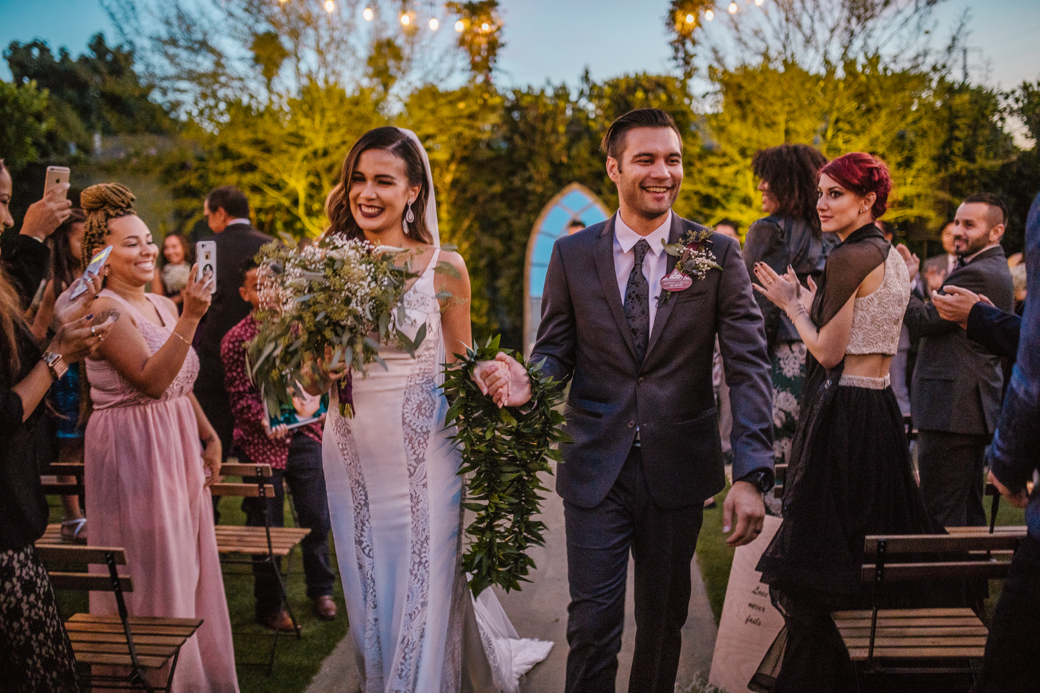 san diego wedding   photographer   newly wed couple walking down aisle with plants between them