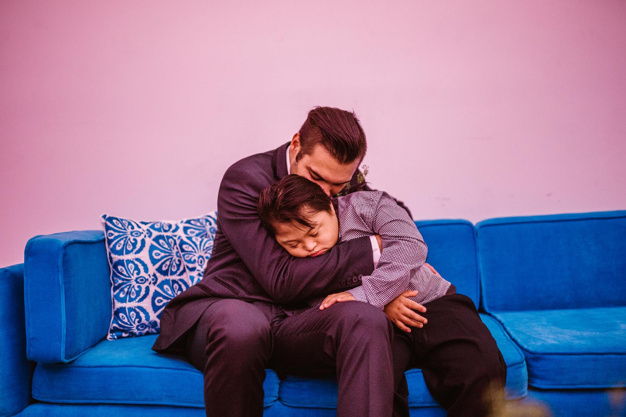 san diego wedding   photographer   groom hugging sleeping child on couch