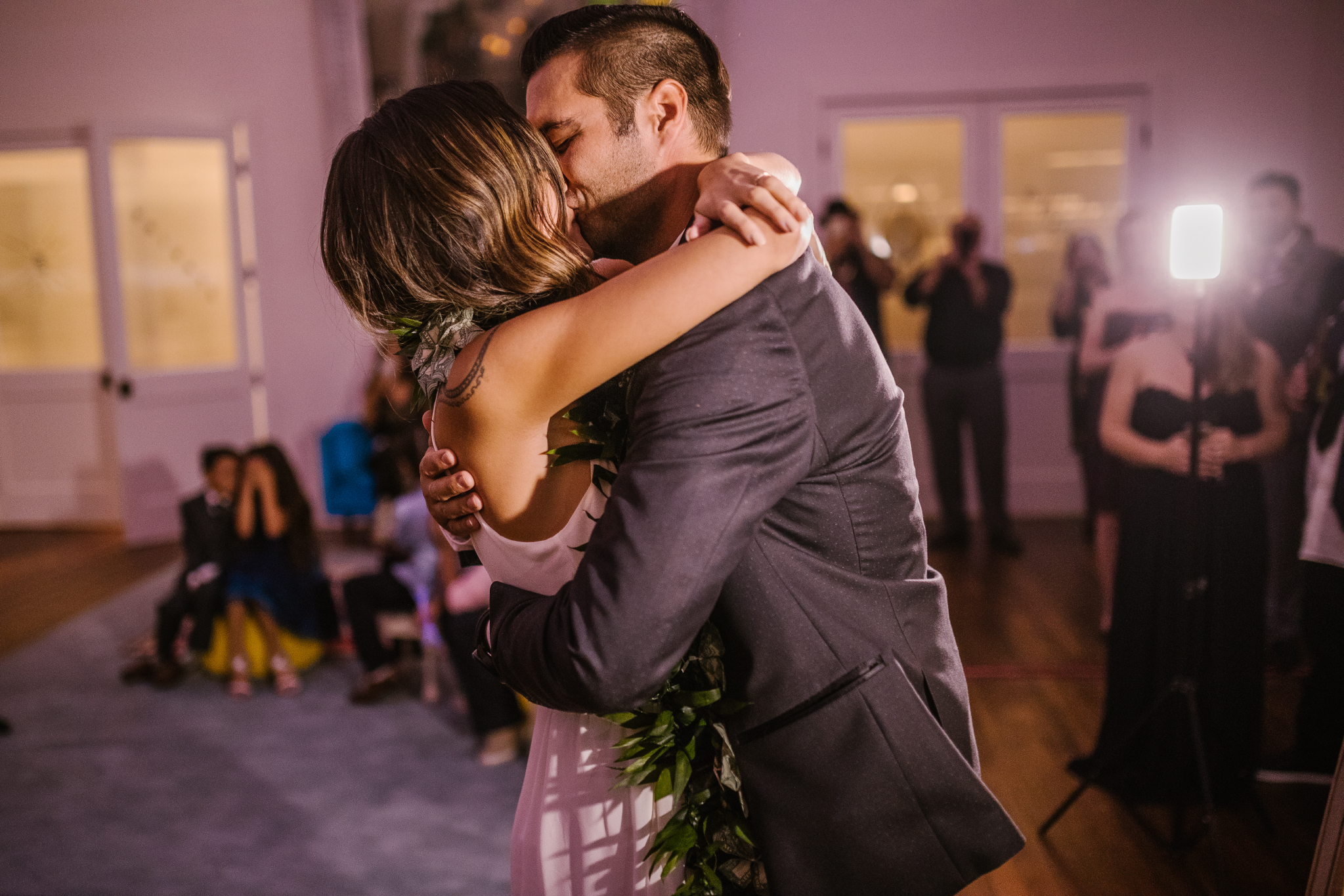 san diego wedding photographer   bride and groom standing and hugging tightly on dance floor with lighting in background