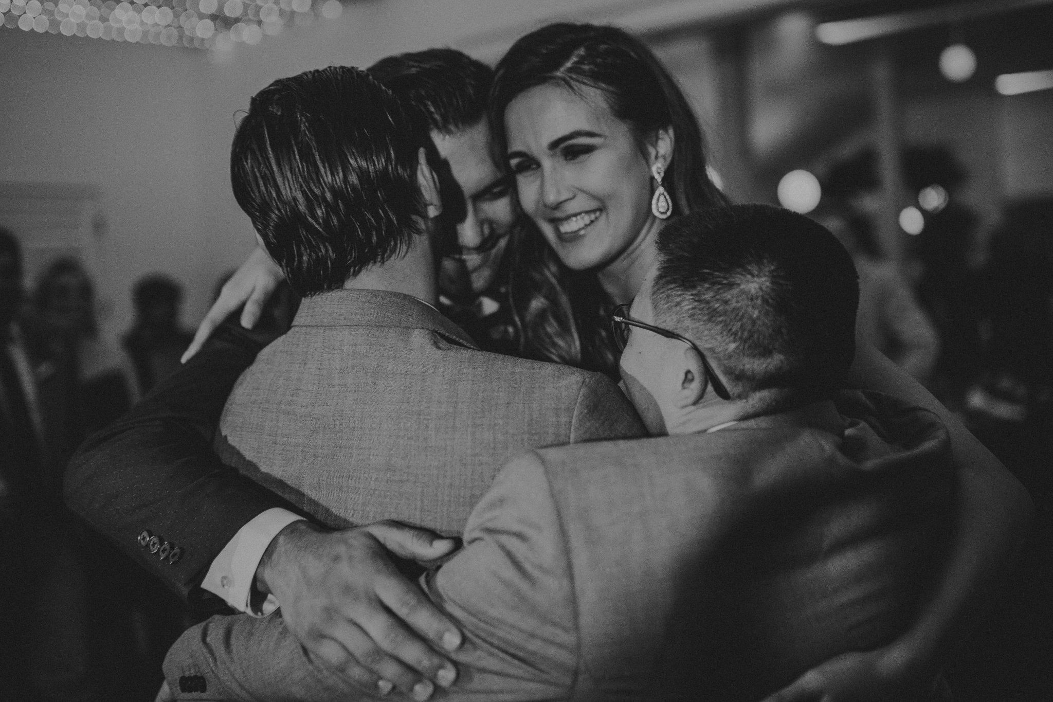 san diego wedding   photographer   monotone picture of bride hugging group of men