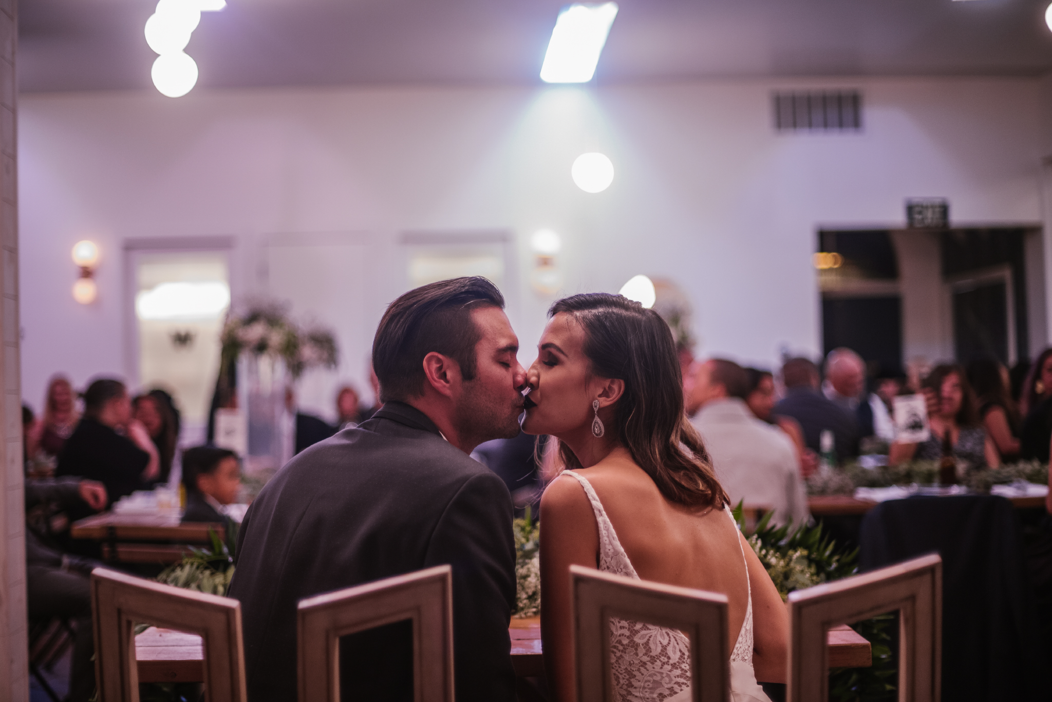 san diego wedding   photographer | bride and groom kissing while sitting down with crowd in   background