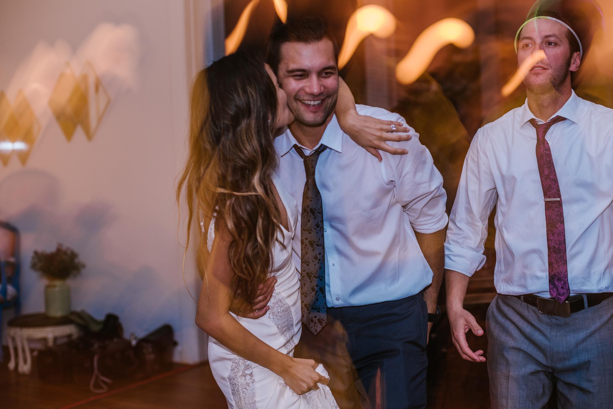 san diego wedding   photographer   bride kissing man on cheek on dance floor