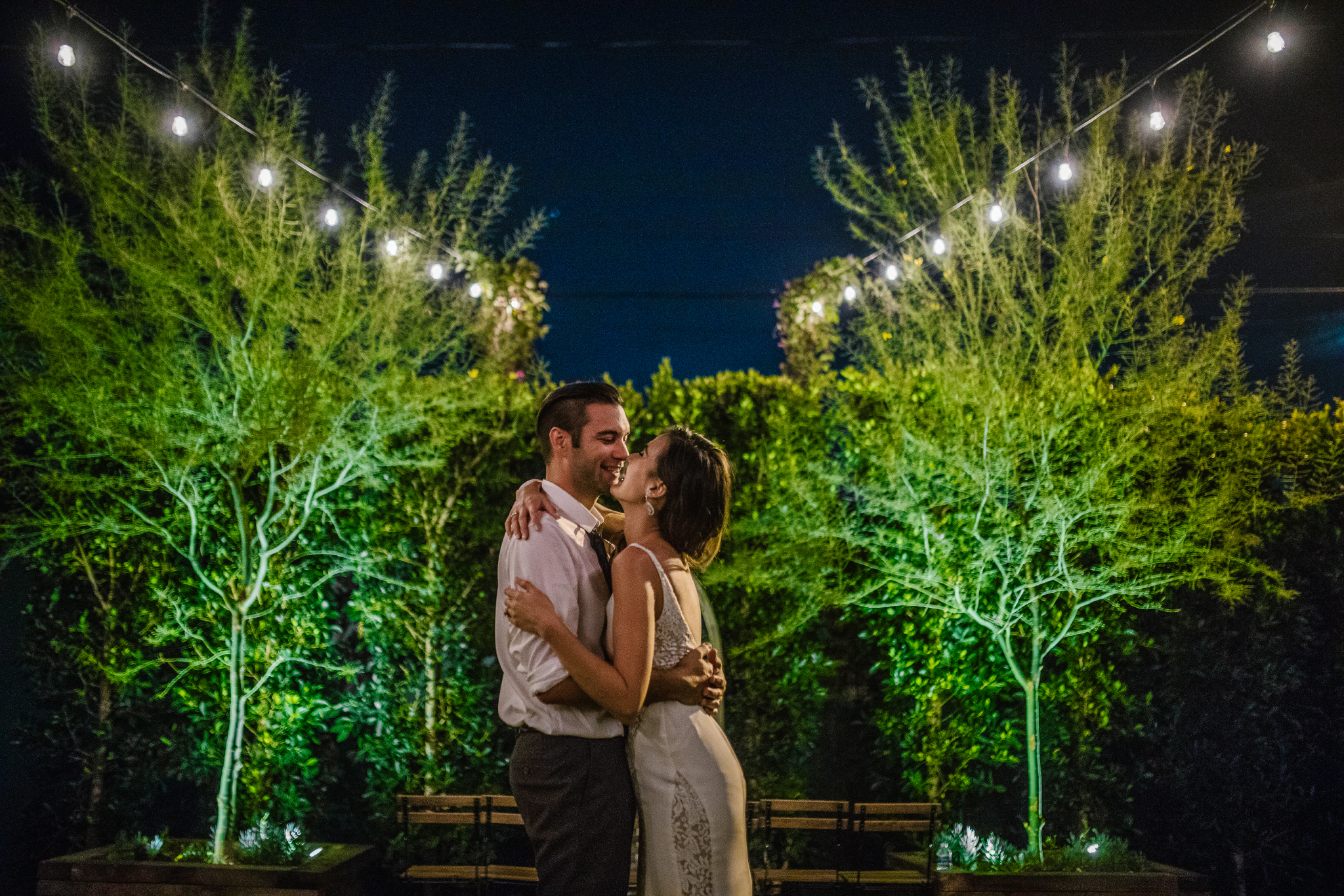 san diego wedding   photographer   bride and groom about to kiss between plants and light