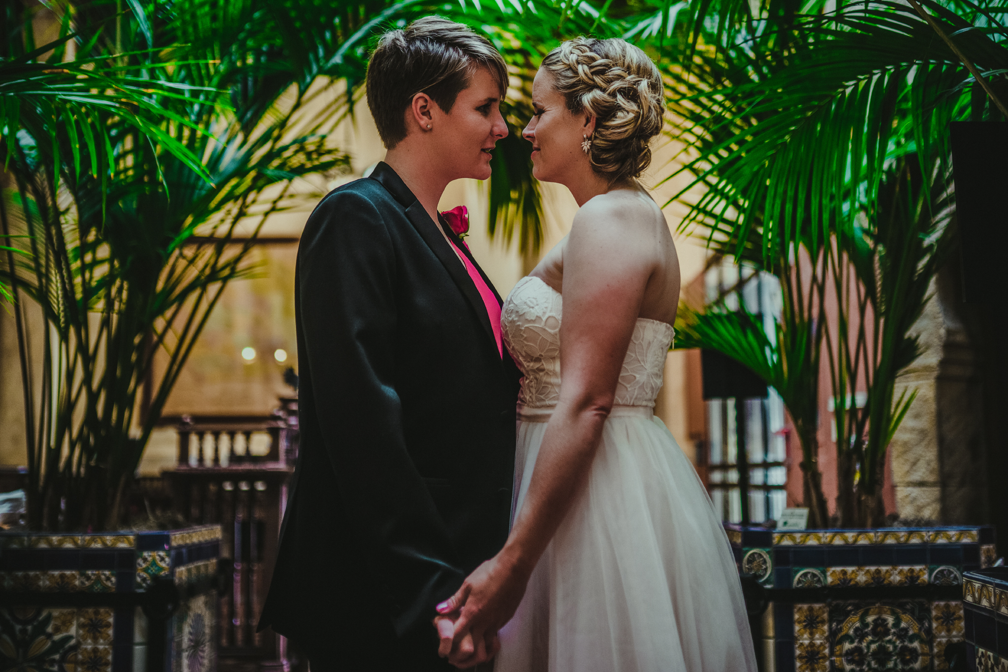 san diego wedding   photographer | women about to kiss each other with potted plants behind them