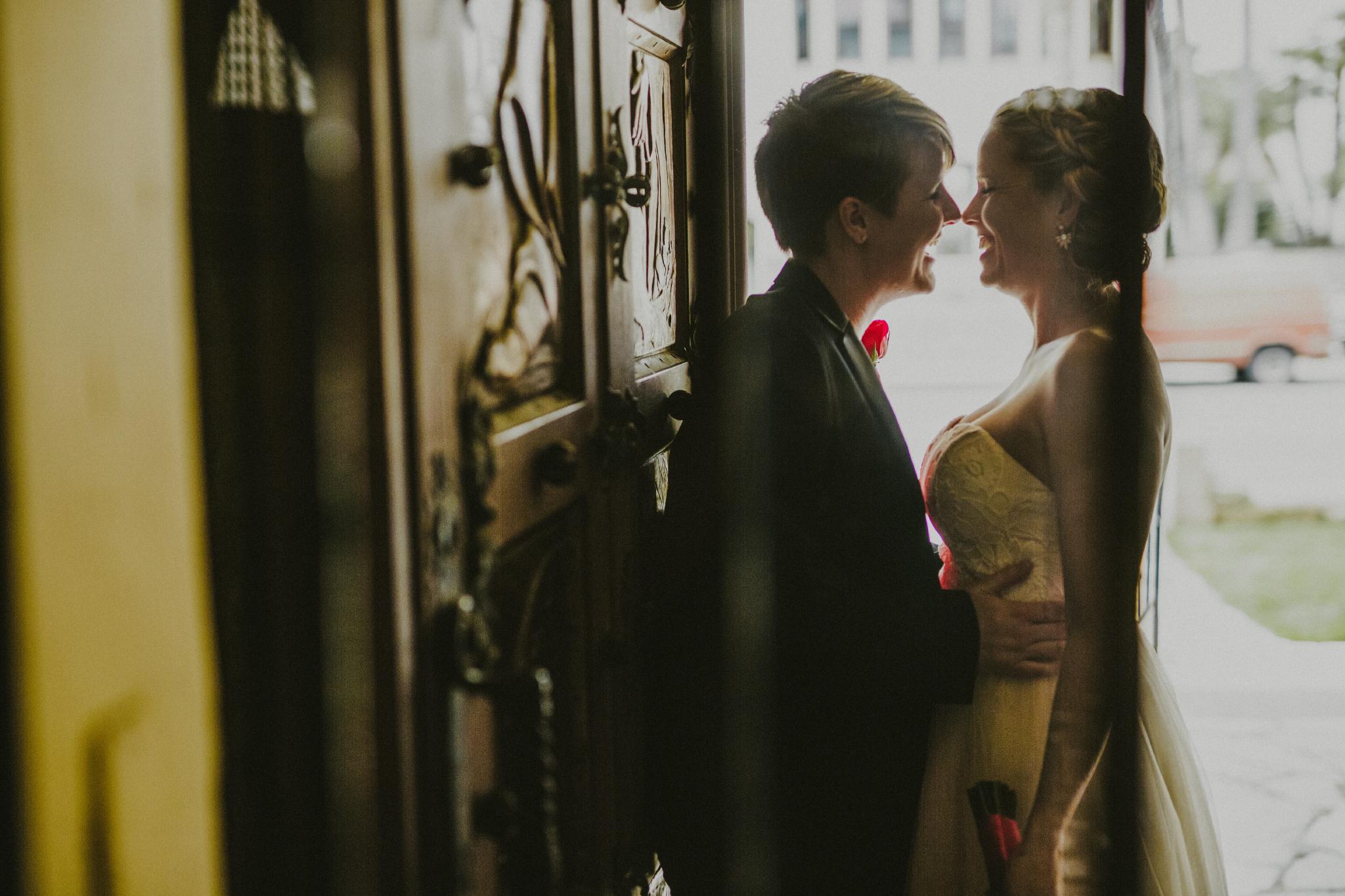 san diego wedding   photographer   woman in blazer holding woman in doorway