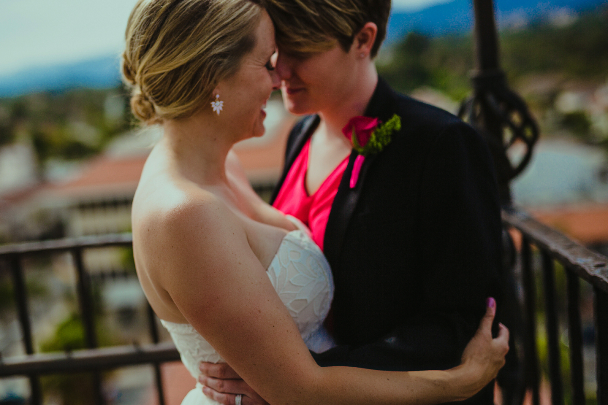 san diego wedding   photographer | women about to kiss with metal railing behind