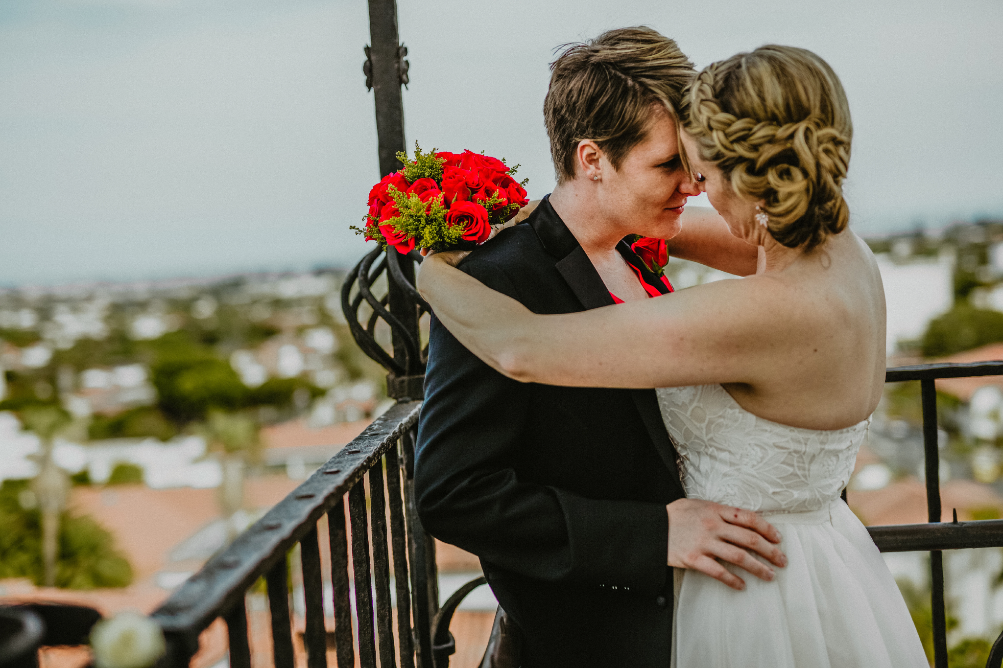 san diego wedding   photographer | women holding each other standing close with railing behind   them