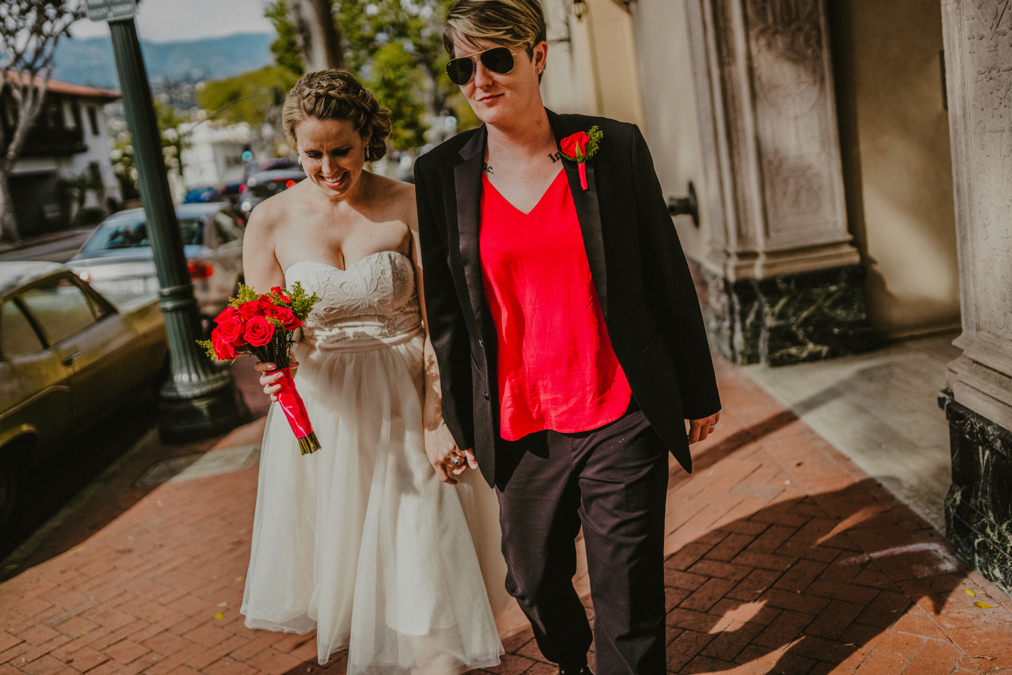 san diego wedding   photographer | woman holding woman's hand walking down sidewalk with bouquet