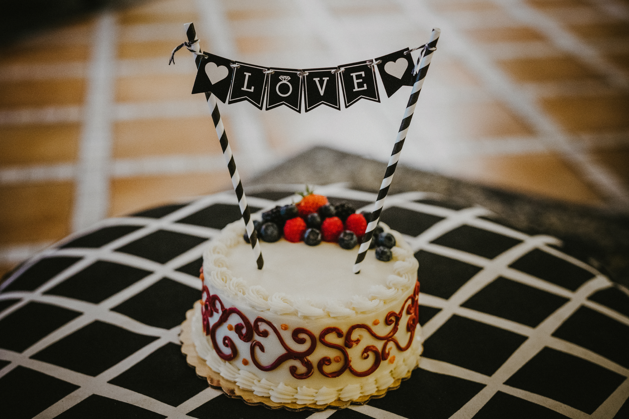 "san diego wedding   photographer | cake with the word ""love"" on streamers"