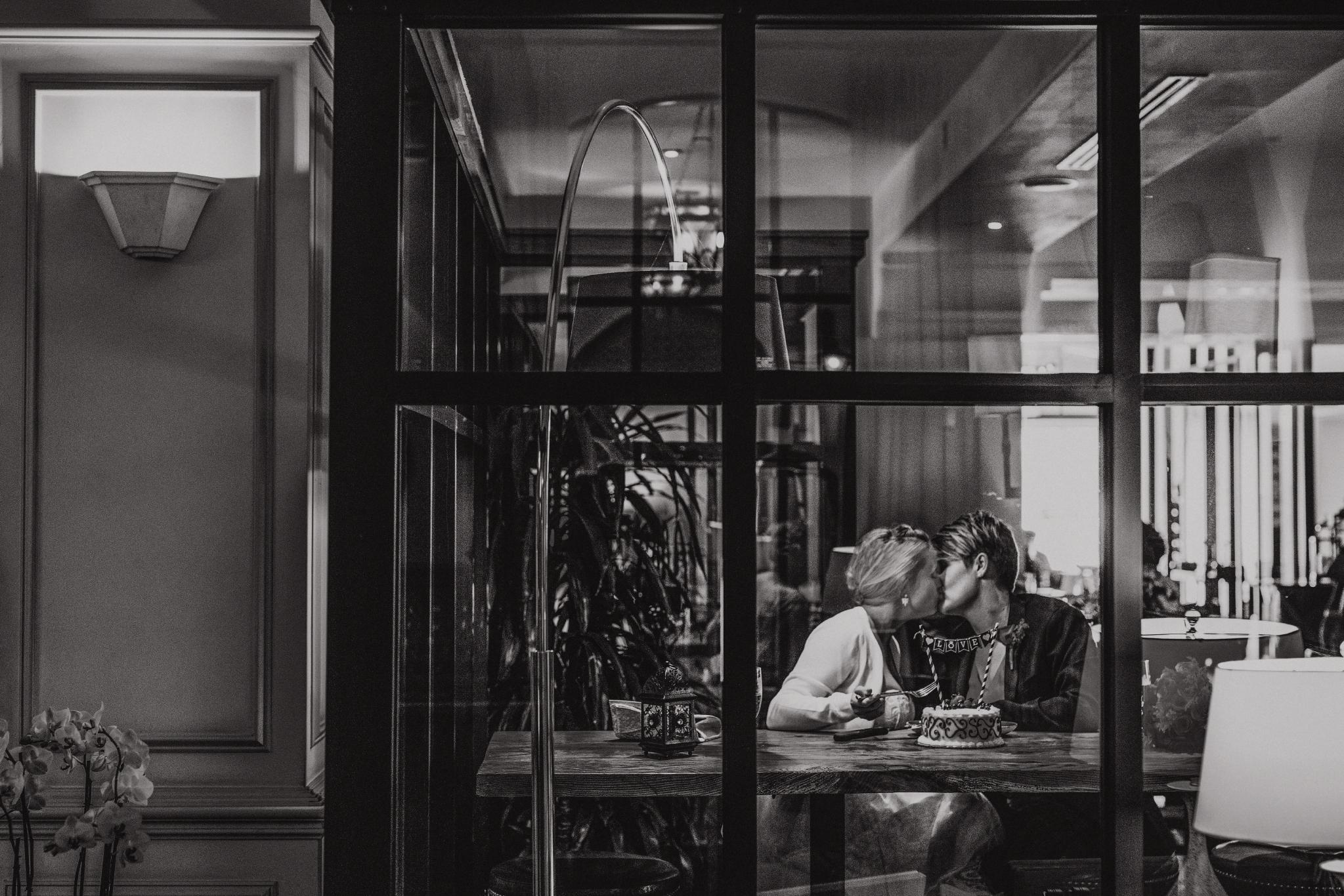san diego wedding   photographer   monotone shot of women kissing seen through window panel