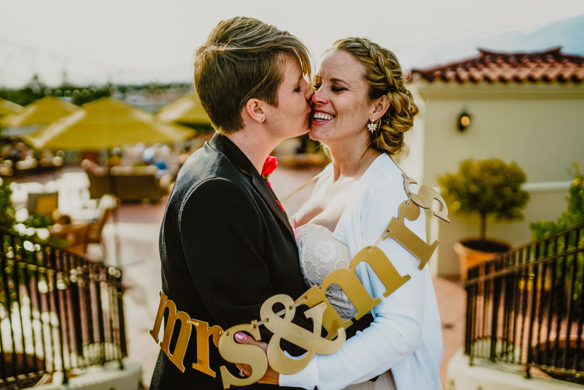 "san diego wedding   photographer | woman kissing smiling woman with ""mrs and mrs""   around them"