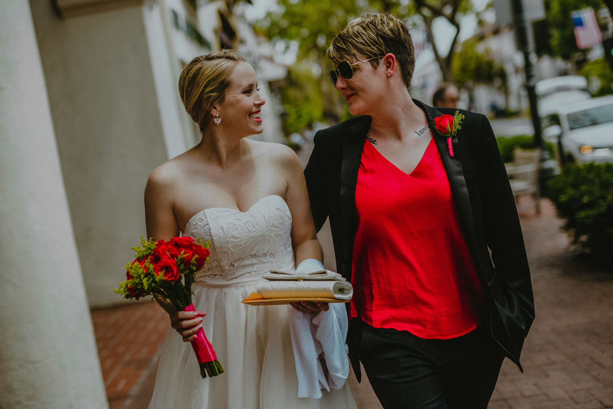 san diego wedding   photographer | woman in white holding purse smiling walking next to woman