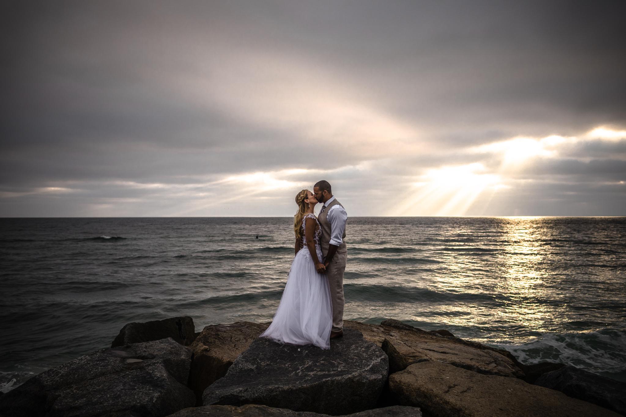san diego wedding   photographer | couple kissing on rocks by the sea