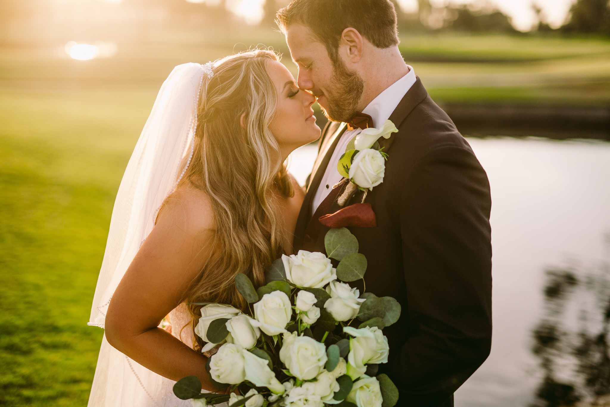 san diego wedding   photographer | couple looking at each other with flowers in front of lake