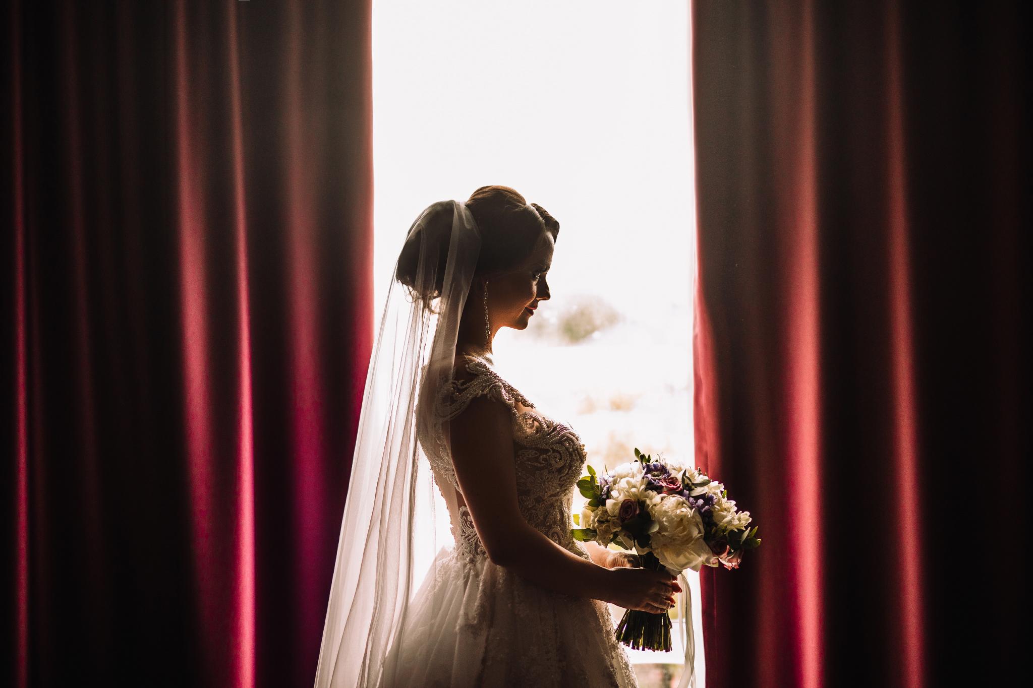 san diego wedding   photographer | woman holding flowers against curtains