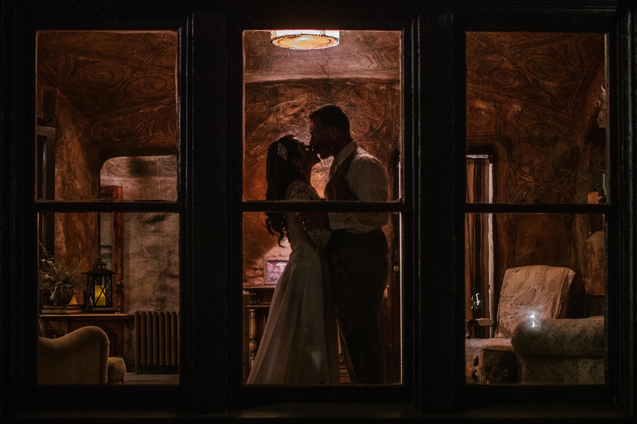 san diego wedding   photographer | couple kissing seen through window
