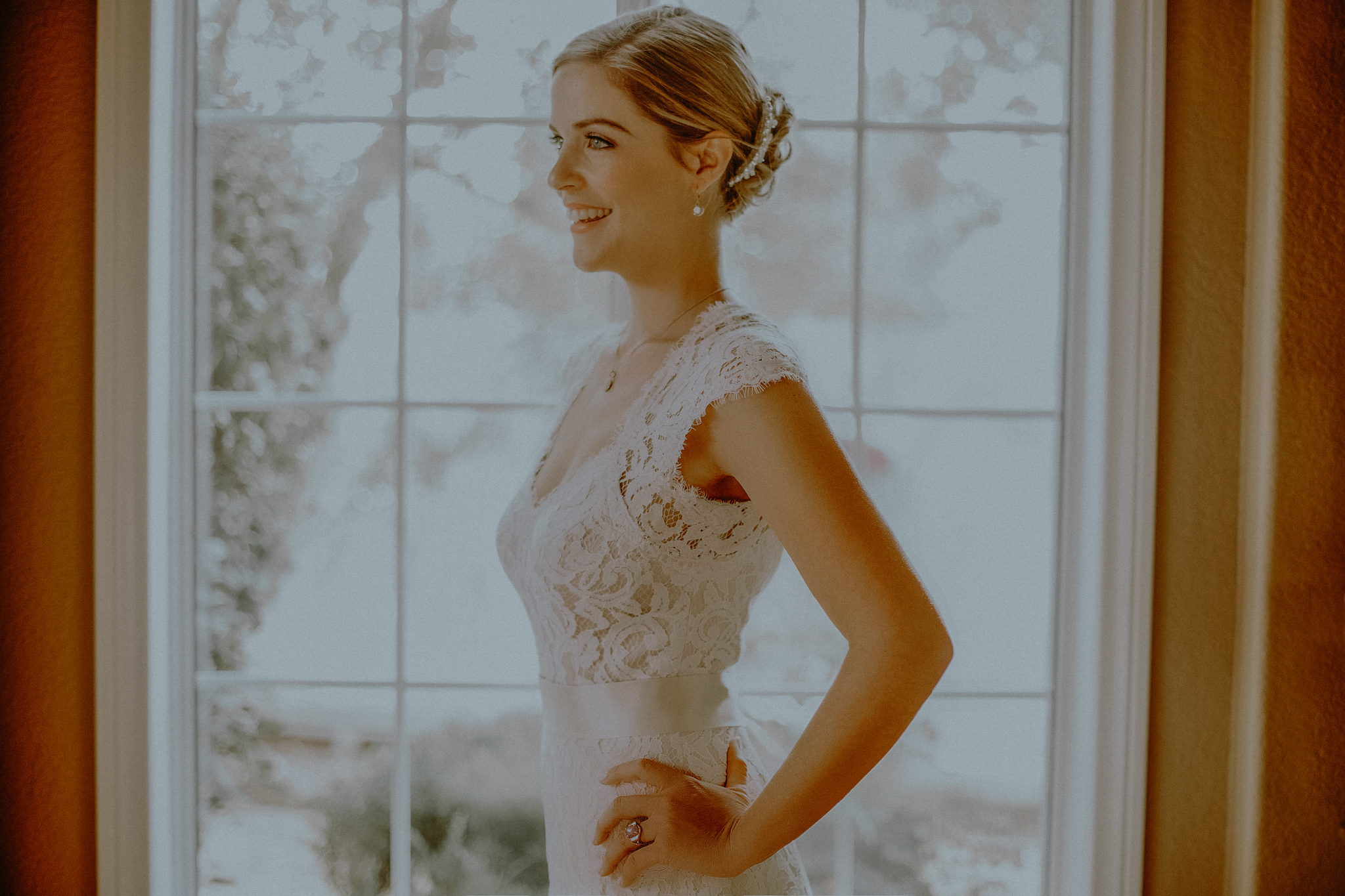 san diego wedding   photographer | woman in dress standing in front of big window
