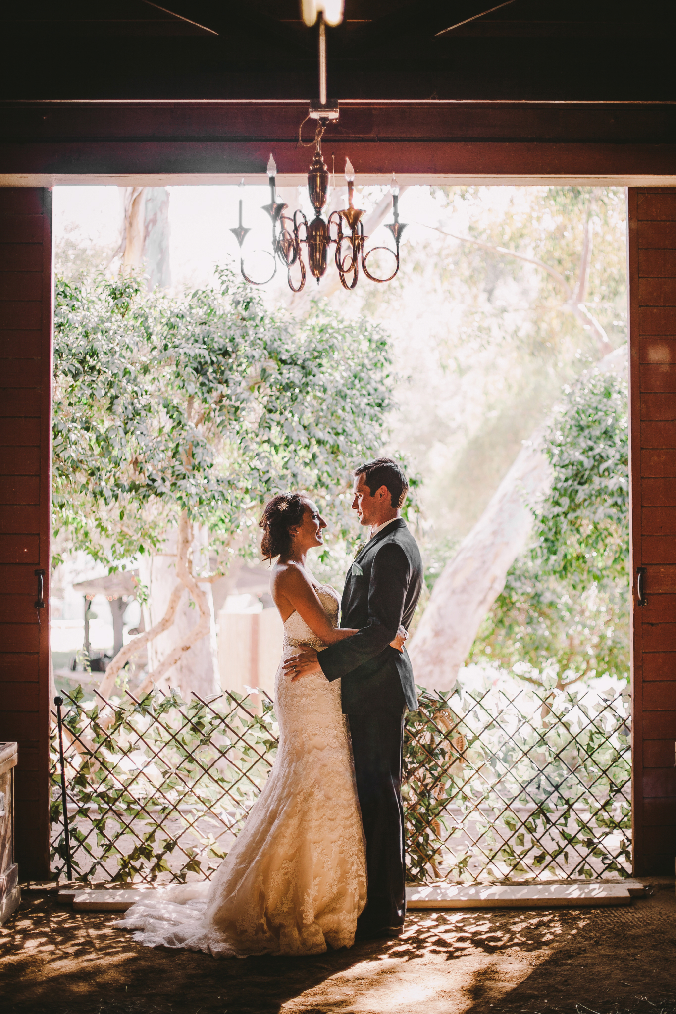 san diego wedding   photographer | couple looking at each other in front of fence