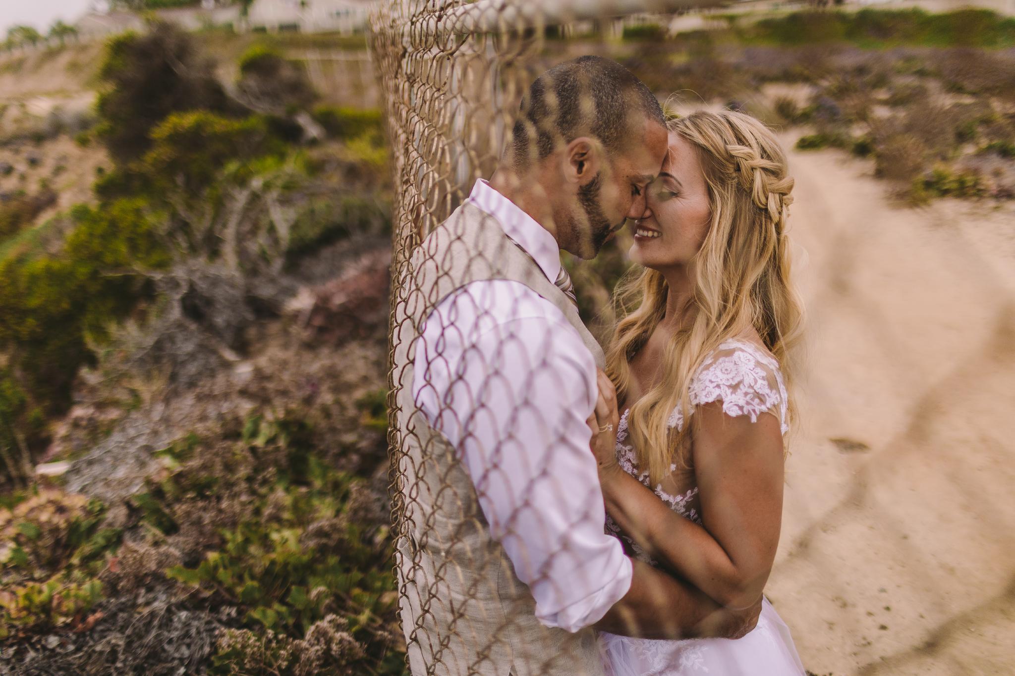 san diego wedding   photographer | couple kissing against fence