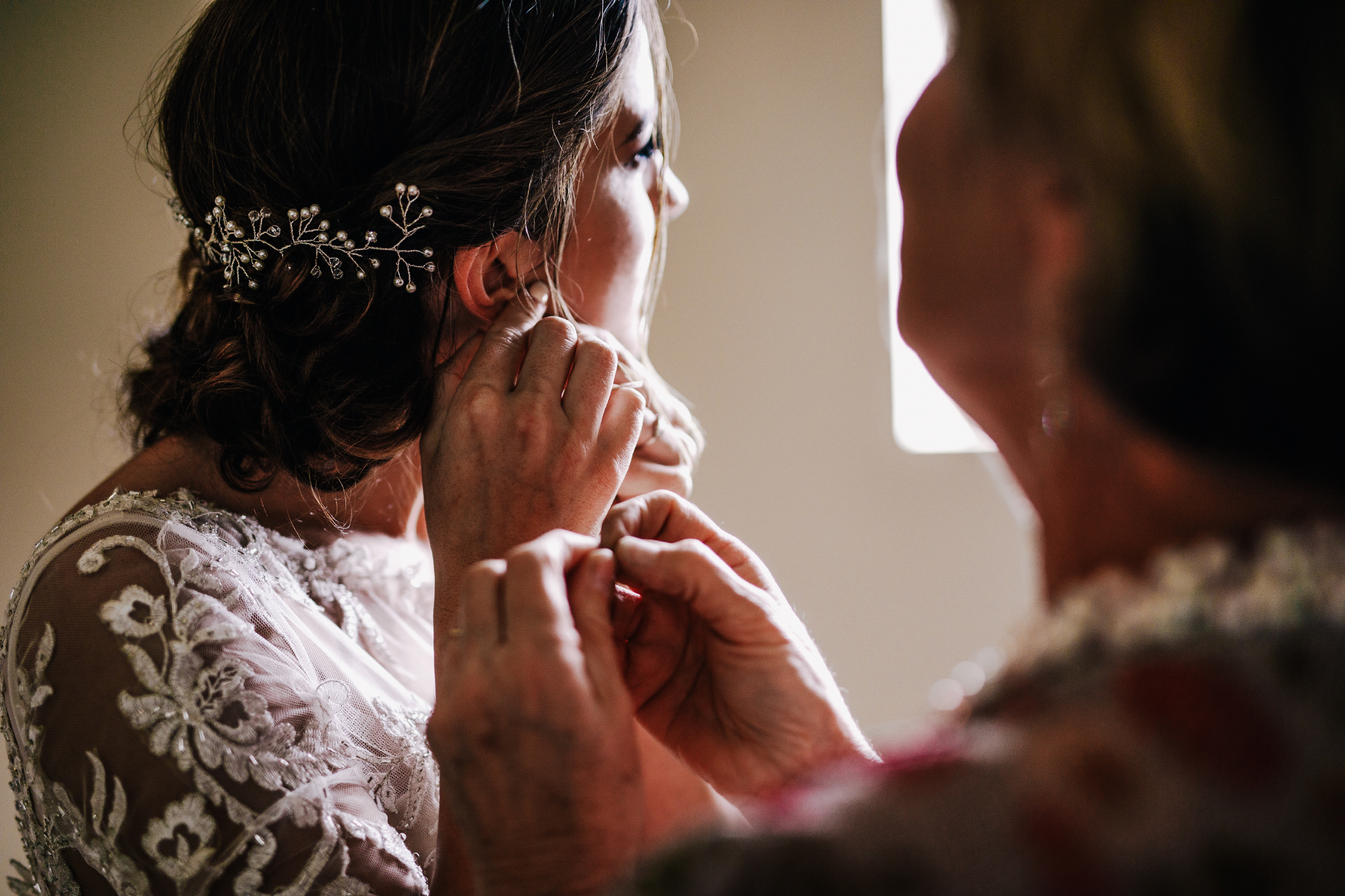 san diego wedding   photographer | bride putting on her earrings with woman in red floral dress   assisting her
