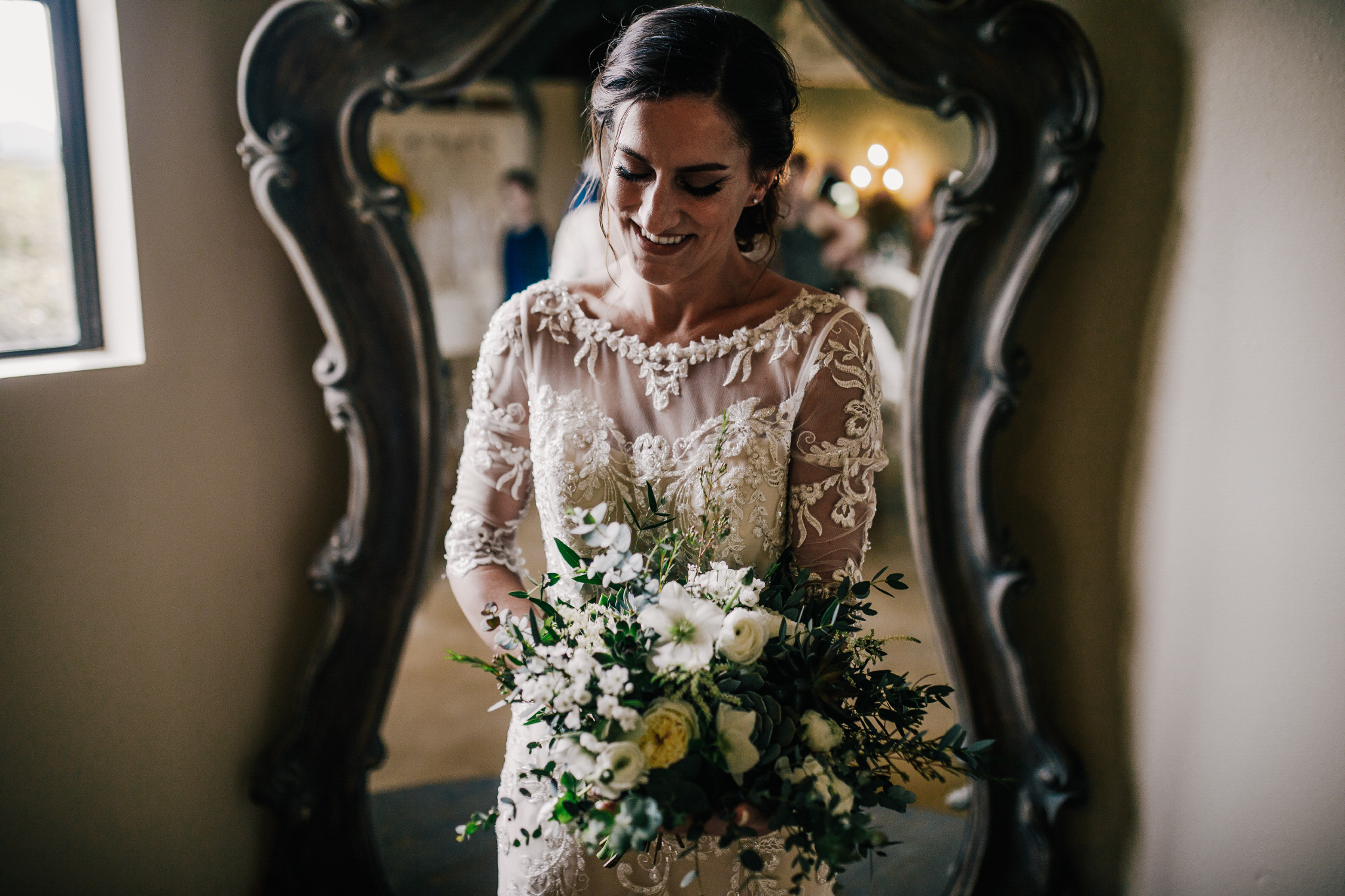 san diego wedding   photographer | bride in her wedding dress holding bouquet of flowers standing   in front of mirror