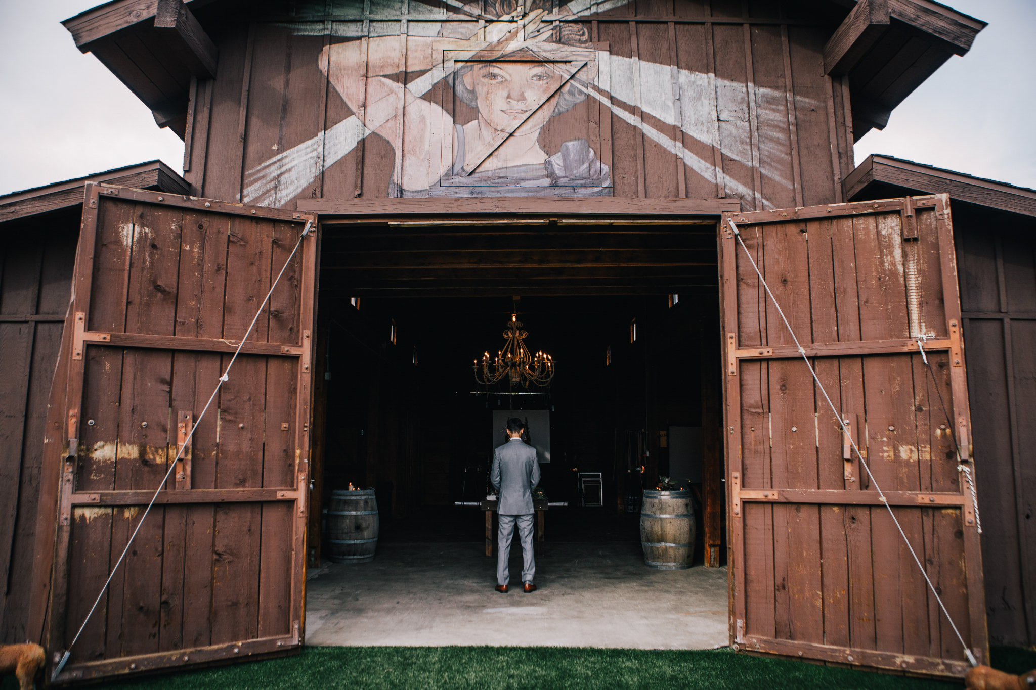 san diego wedding   photographer | groom in grey suit standing in barn with chandelier